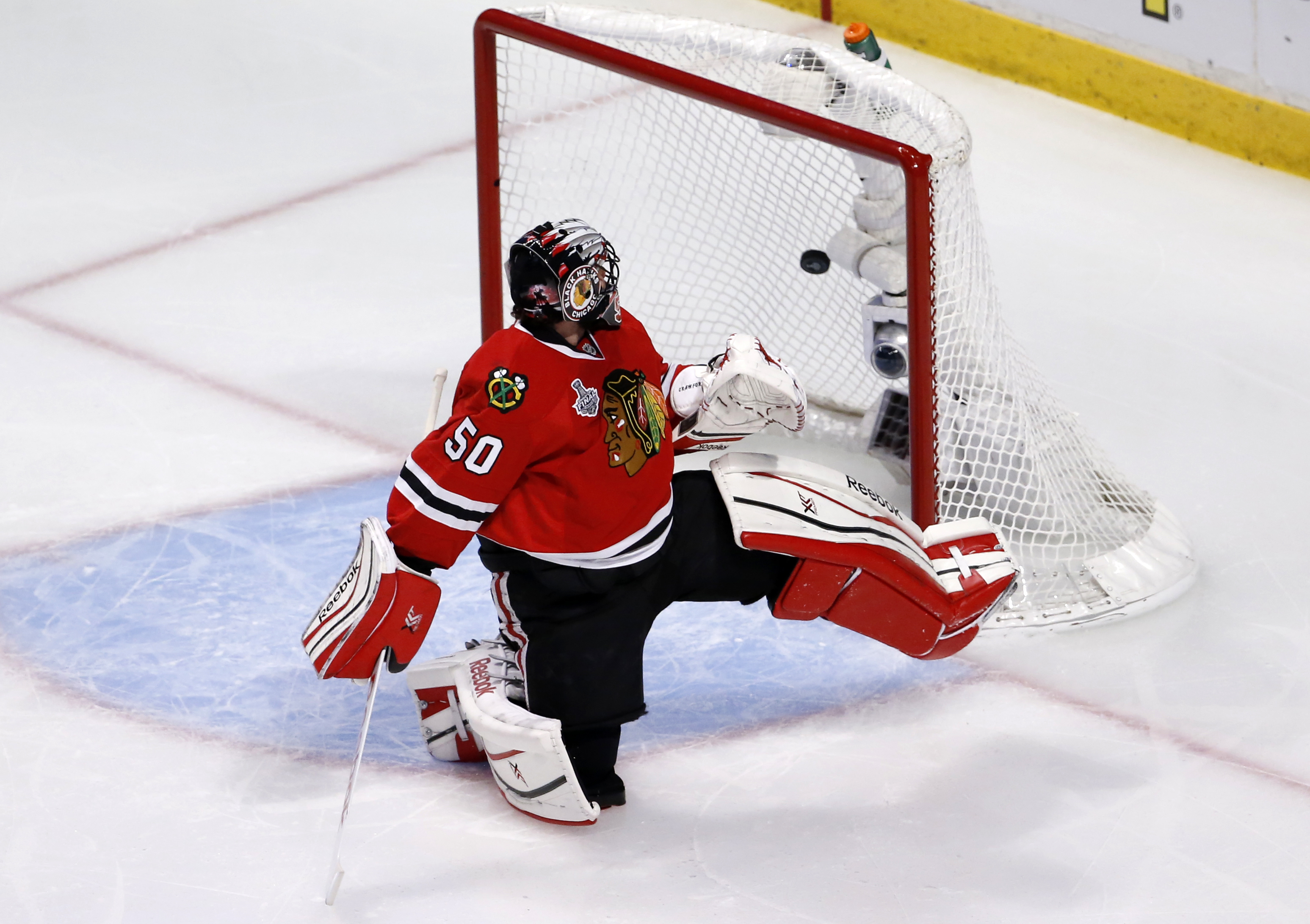A shot by Tampa Bay Lightning's Ryan Callahan slips past Chicago Blackhawks goalie Corey Crawford for a goal during the first period in Game 3 of the NHL hockey Stanley Cup Final on Monday, June 8, 2015, in Chicago. (AP Photo/Charles Rex Arbogast)