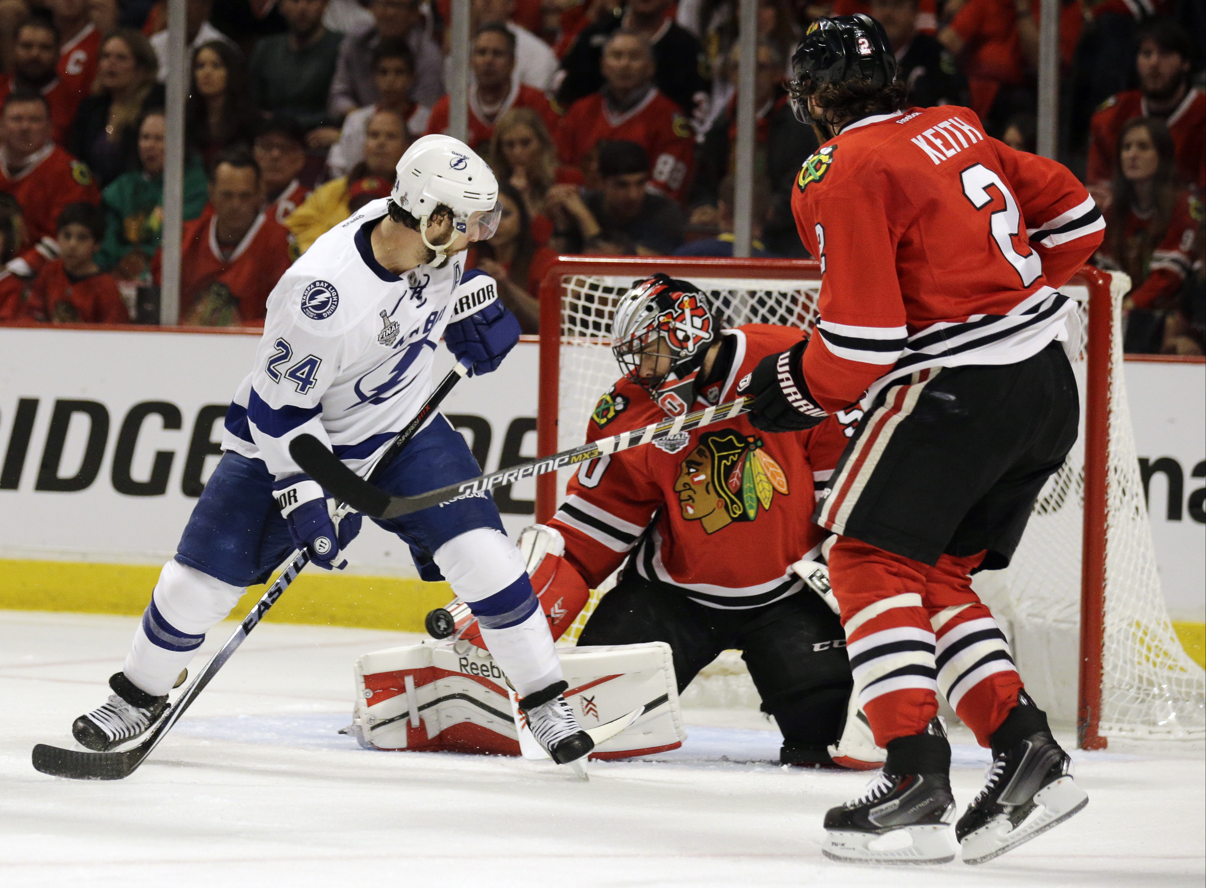 Chicago Blackhawks goalie Corey Crawford, center, keeps his eye on the puck as teammate Duncan Keith, right, and Tampa Bay Lightning's Ryan Callahan, left, watch during the first period in Game 4 of the NHL hockey Stanley Cup Final Wednesday, June 10, 201