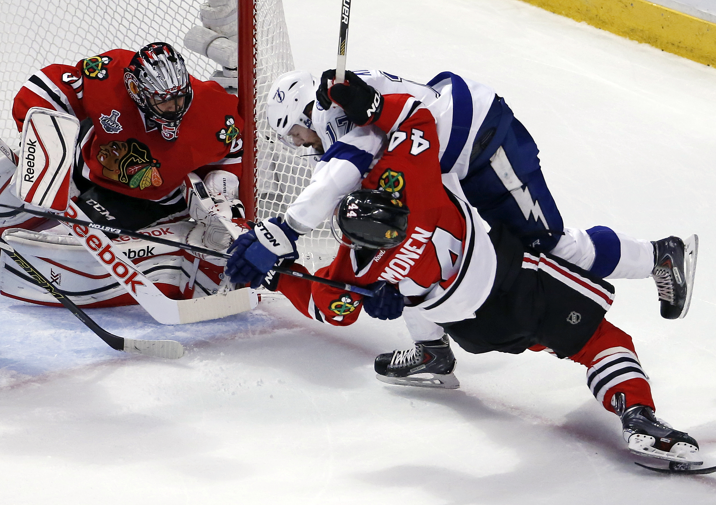 Chicago Blackhawks' Kimmo Timonen, front right, and Tampa Bay Lightning's Alex Killorn get tangled up as Blackhawks goalie Corey Crawford, left, watches during the first period in Game 4 of the NHL hockey Stanley Cup Final Wednesday, June 10, 2015, in Chi