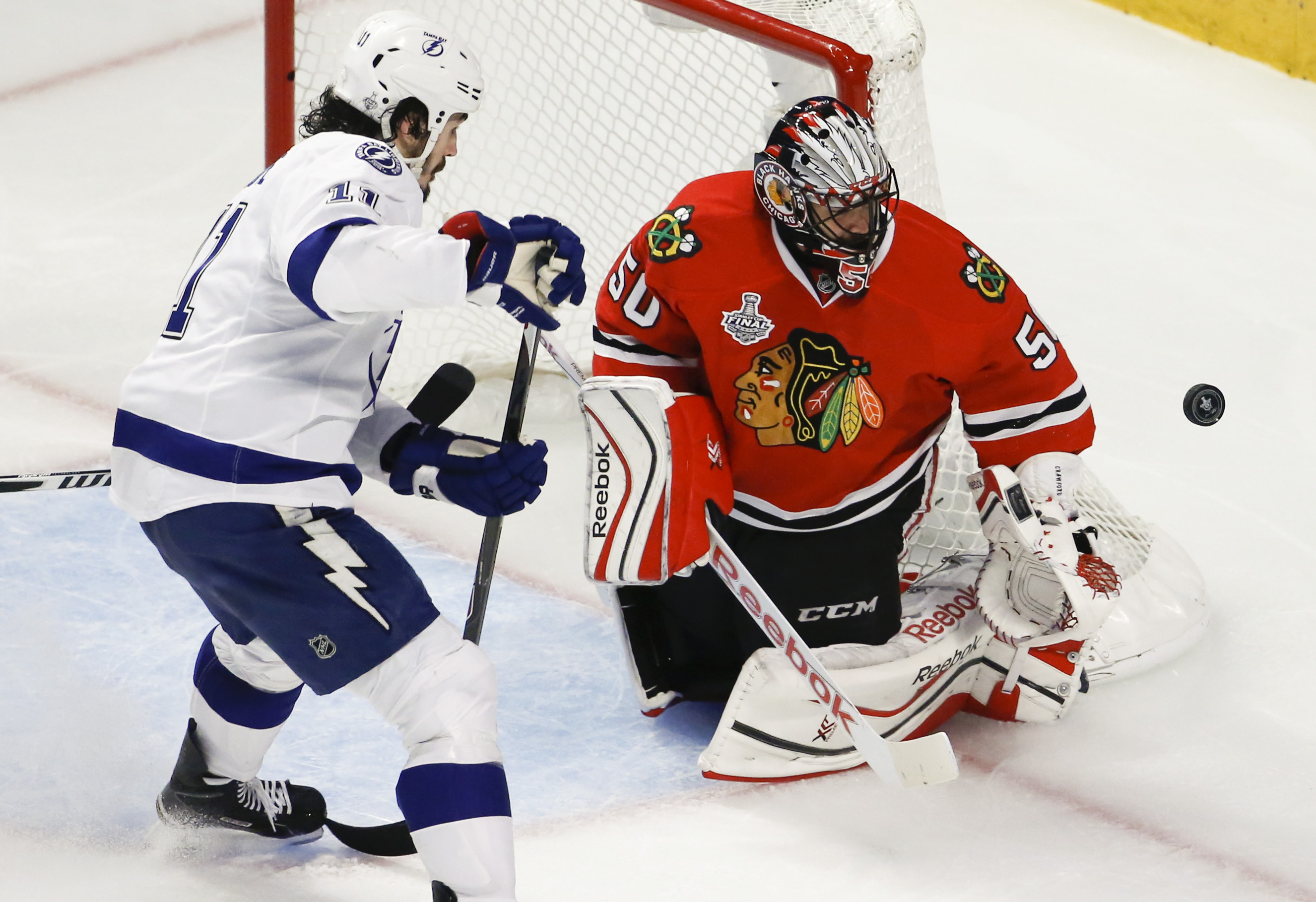 Chicago Blackhawks goalie Corey Crawford, right, deflects a puck as Tampa Bay Lightning's Brian Boyle watches during the third period in Game 4 of the NHL hockey Stanley Cup Final Wednesday, June 10, 2015, in Chicago. (AP Photo/Charles Rex Arbogast)