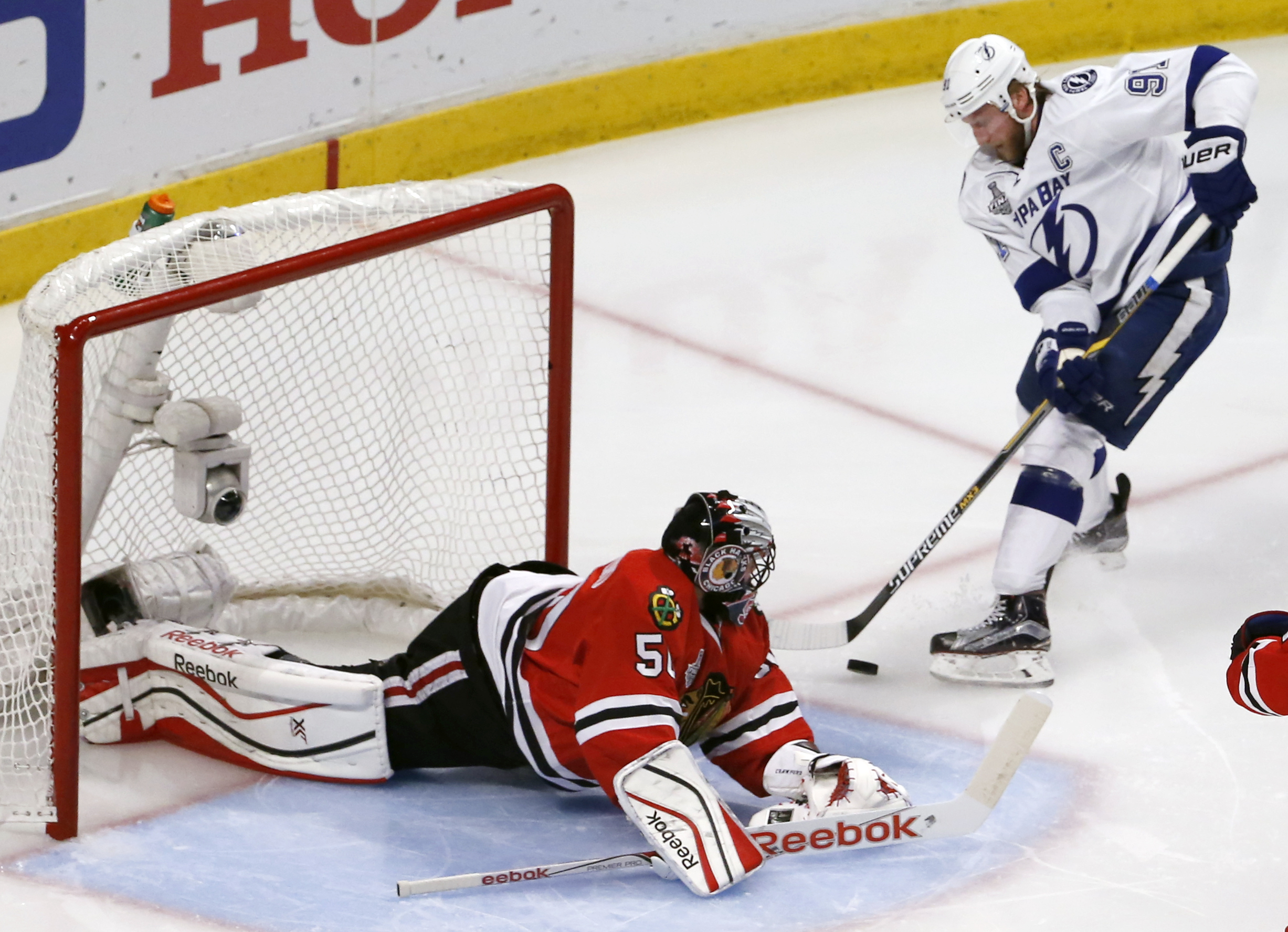 Chicago Blackhawks goalie Corey Crawford, left, makes a save on a shot by Tampa Bay Lightning's Steven Stamkos during the second period in Game 6 of the NHL hockey Stanley Cup Final series on Monday, June 15, 2015, in Chicago. (AP Photo/Charles Rex Arboga