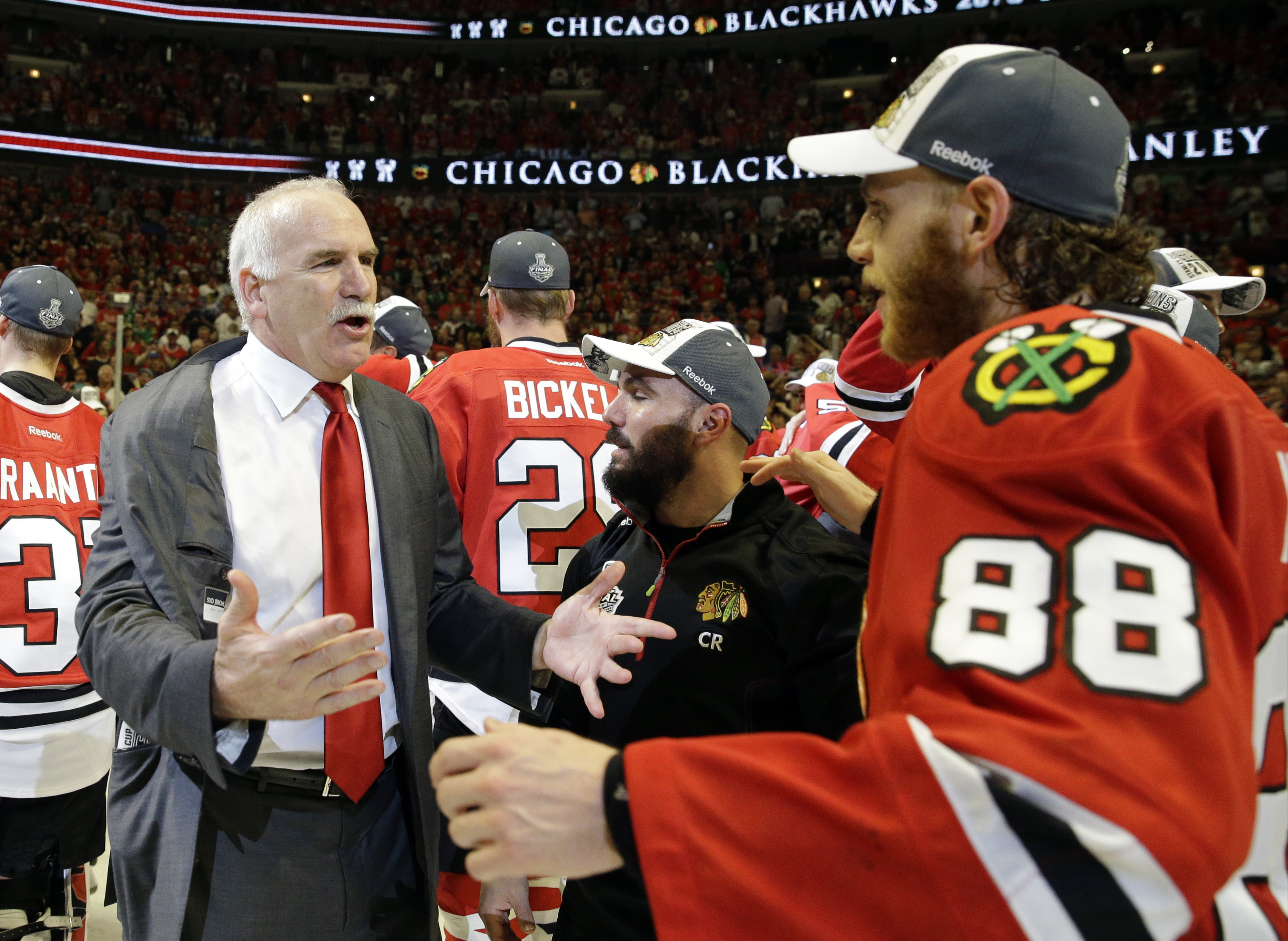 Chicago Blackhawks head coach Joel Quenneville celebrates with Patrick Kane (88) after defeating the Tampa Bay Lightning in Game 6 of the NHL hockey Stanley Cup Final series on Monday, June 15, 2015, in Chicago. The Blackhawks defeated the Lightning 2-0 t