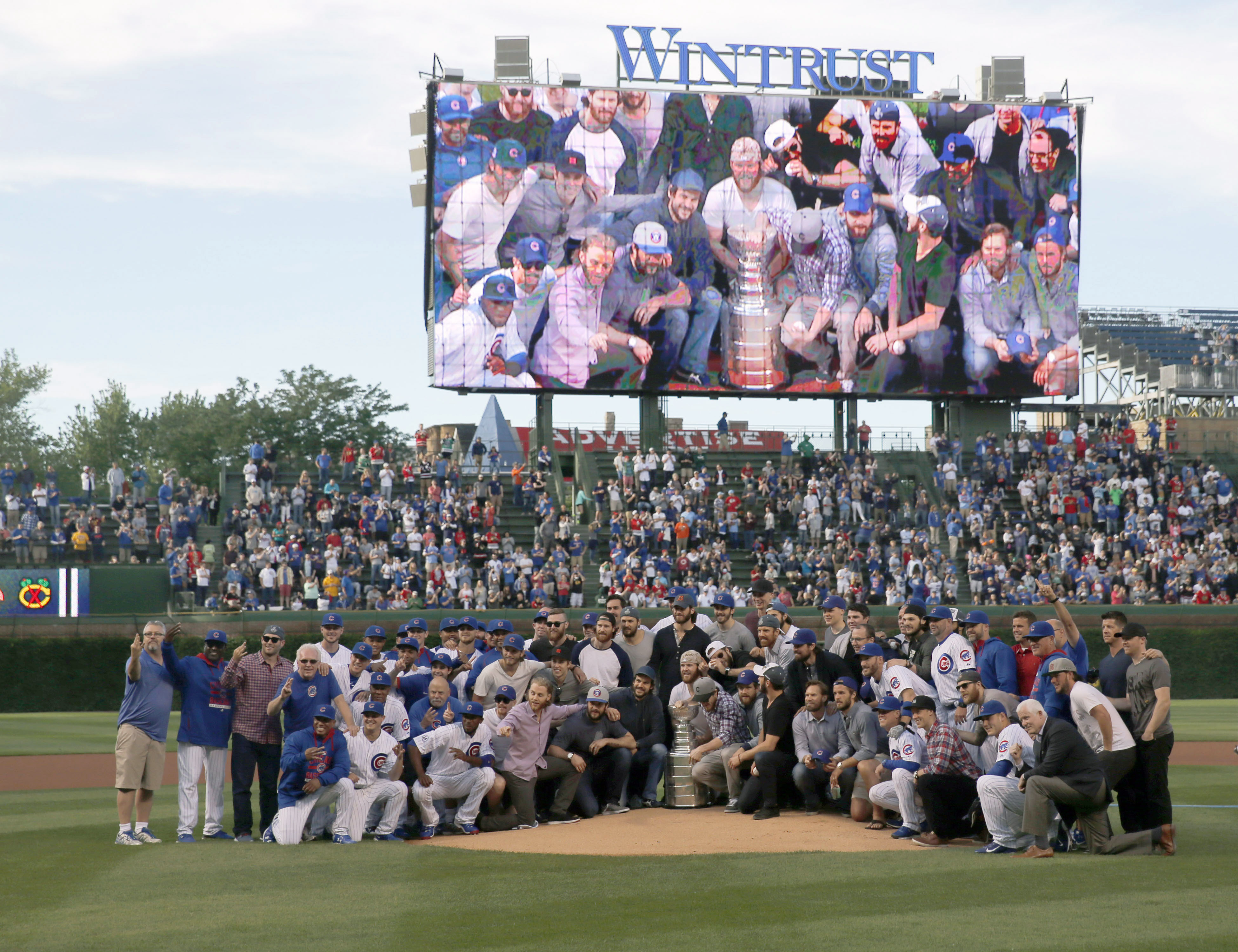 The Chicago Cubs and Blackhawks pose for a photo with the Stanley Cup on the pitcher's mound before an interleague baseball game between the Cubs and Cleveland Indians Tuesday, June 16, 2015, in Chicago. (AP Photo/Charles Rex Arbogast)