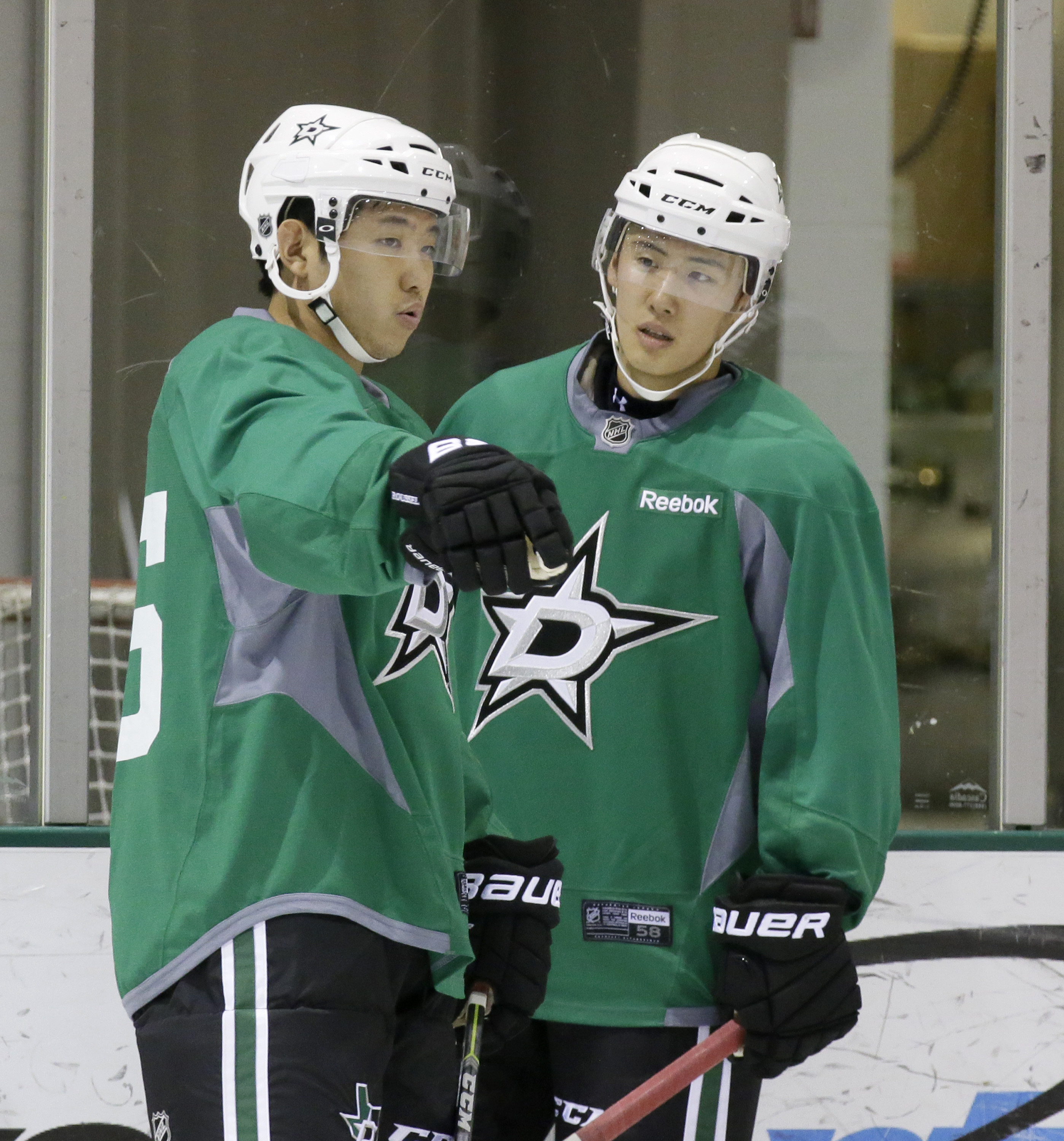 Wonjun Kim, right, of South Korea, listens to fellow South Korean Jinhui Ahn during a Dallas Stars development hockey camp at the team's practice facility in Frisco, Texas, Thursday, July 9, 2015. South Korean players from the Asia League Ice Hockey are w