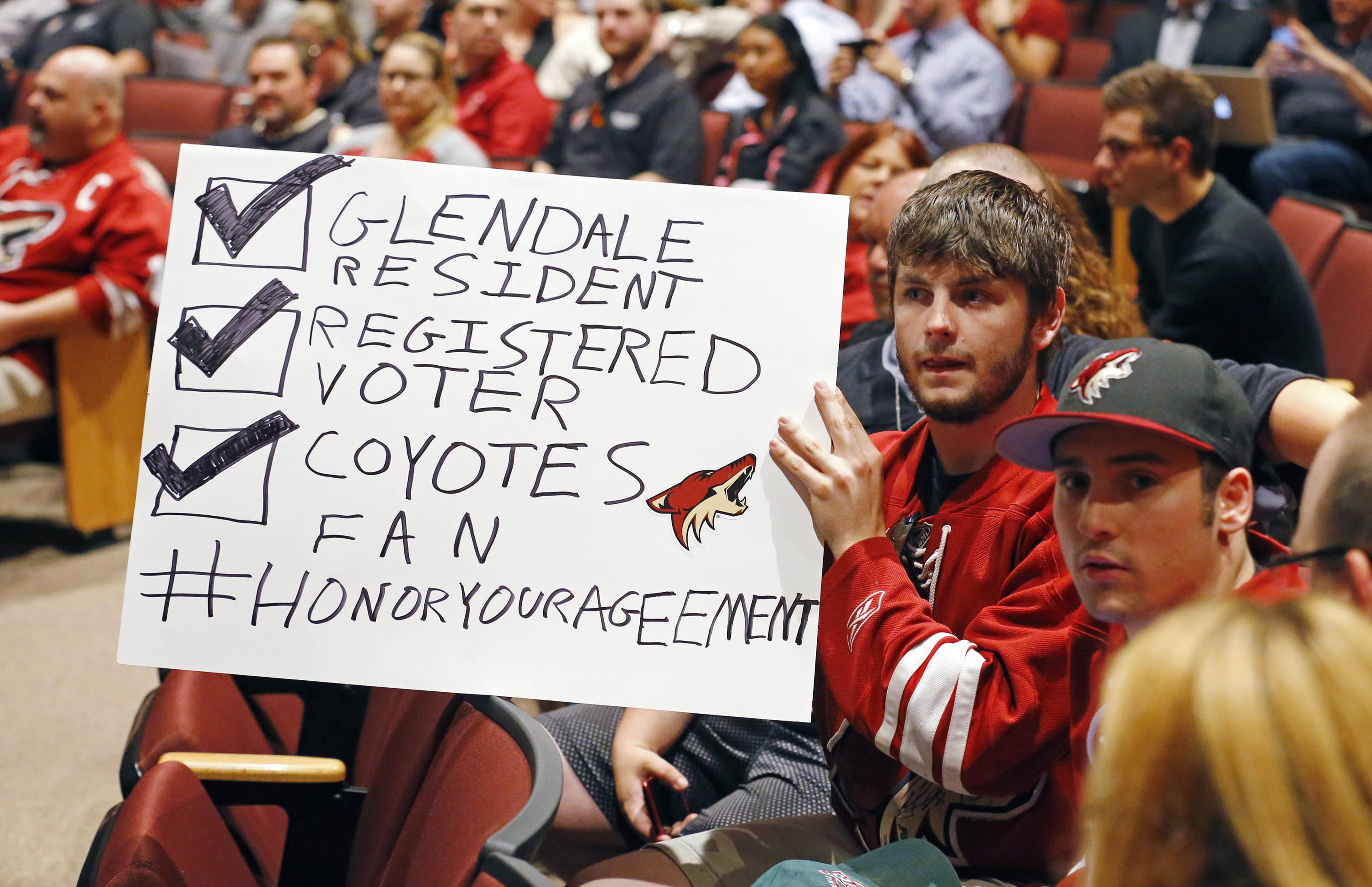 FILE - In this Wednesday, June 10, 2015, file photo, Arizona Coyotes fans Chris Webb, second from right, and Andrew Hill  show their support for their team as the Glendale Council votes whether to back out of an arena lease agreement with the NHL team dur