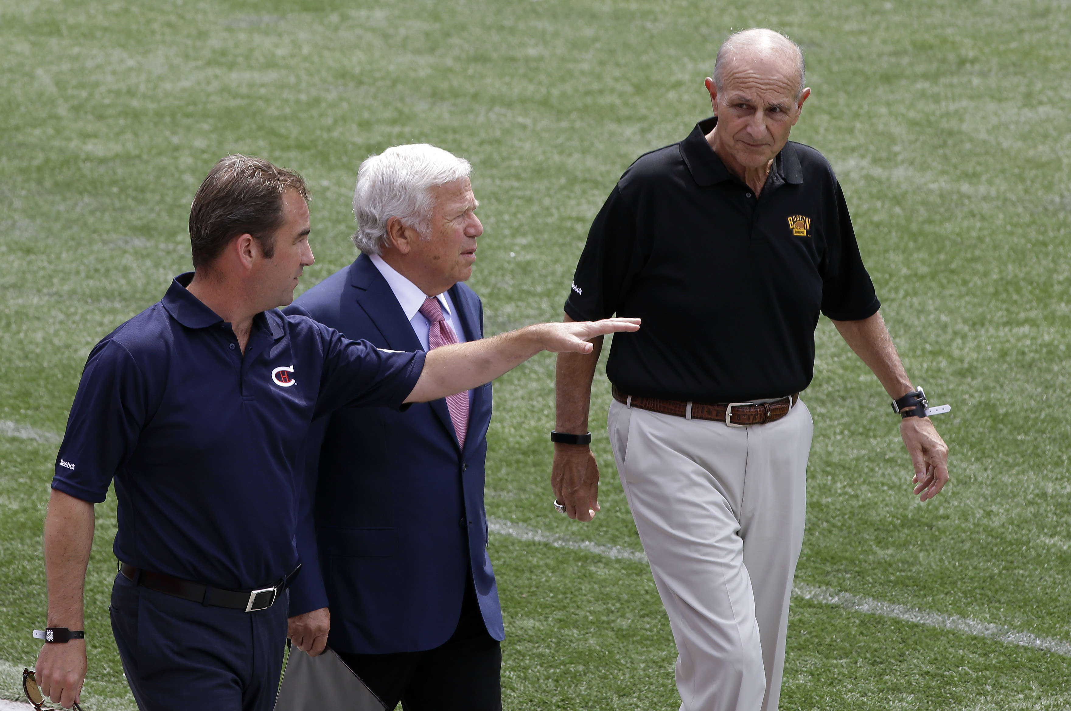 Montreal Canadiens owner Geoff Molson, left, walks on the field at Gillette Stadium with New England Patriots owner Robert Kraft, center, and Boston Bruins owner Jeremy Jacobs during an event Wednesday, July 29, 2015, in Foxborough, Mass., to promote the