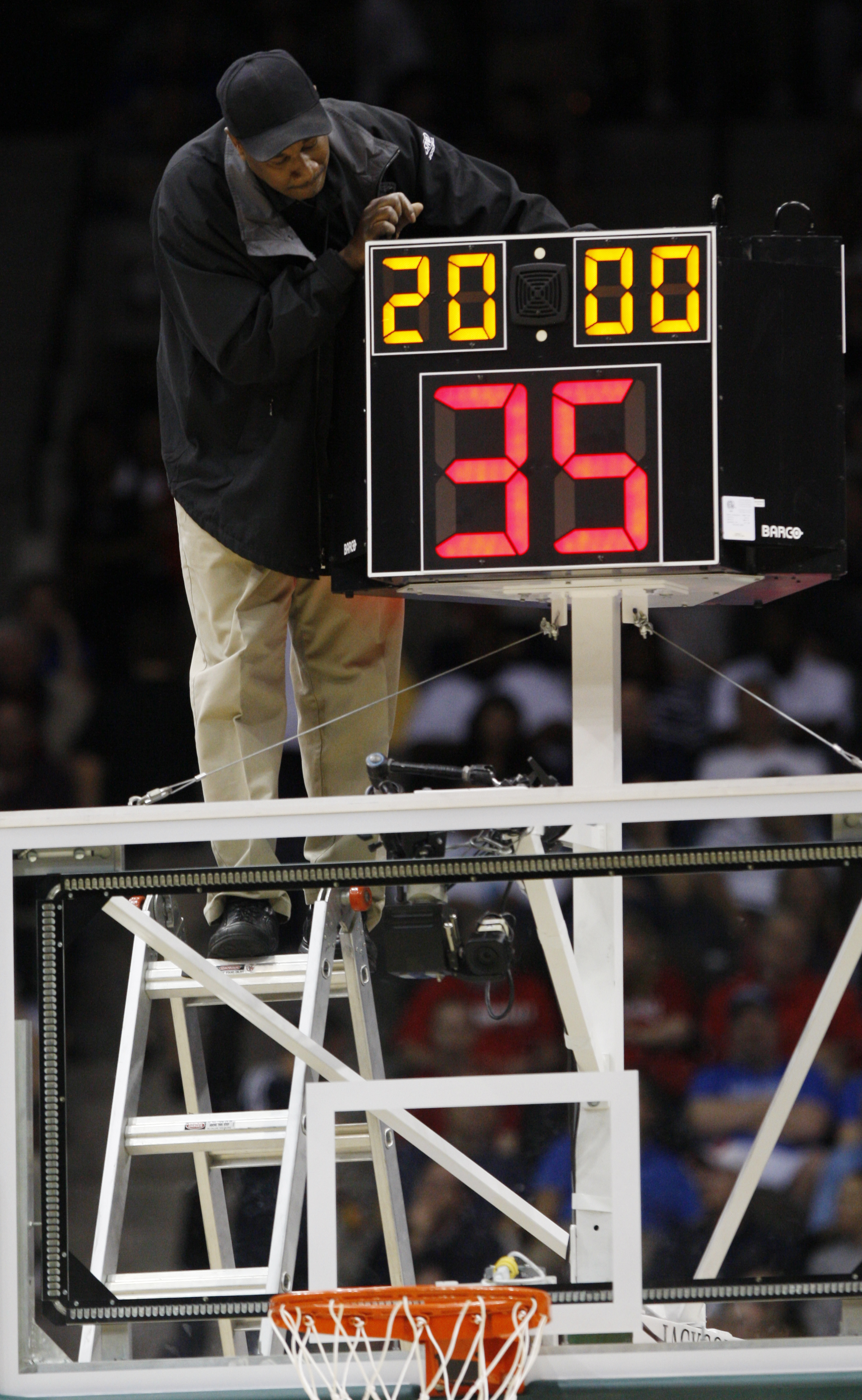 FILE - In this March 19, 2010, file photo,a technician adjusts a shot clock after it malfunctioned and delayed the start of the California against Louisville NCAA first-round college basketball game in Jacksonville, Fla. The NCAA men's basketball rules co