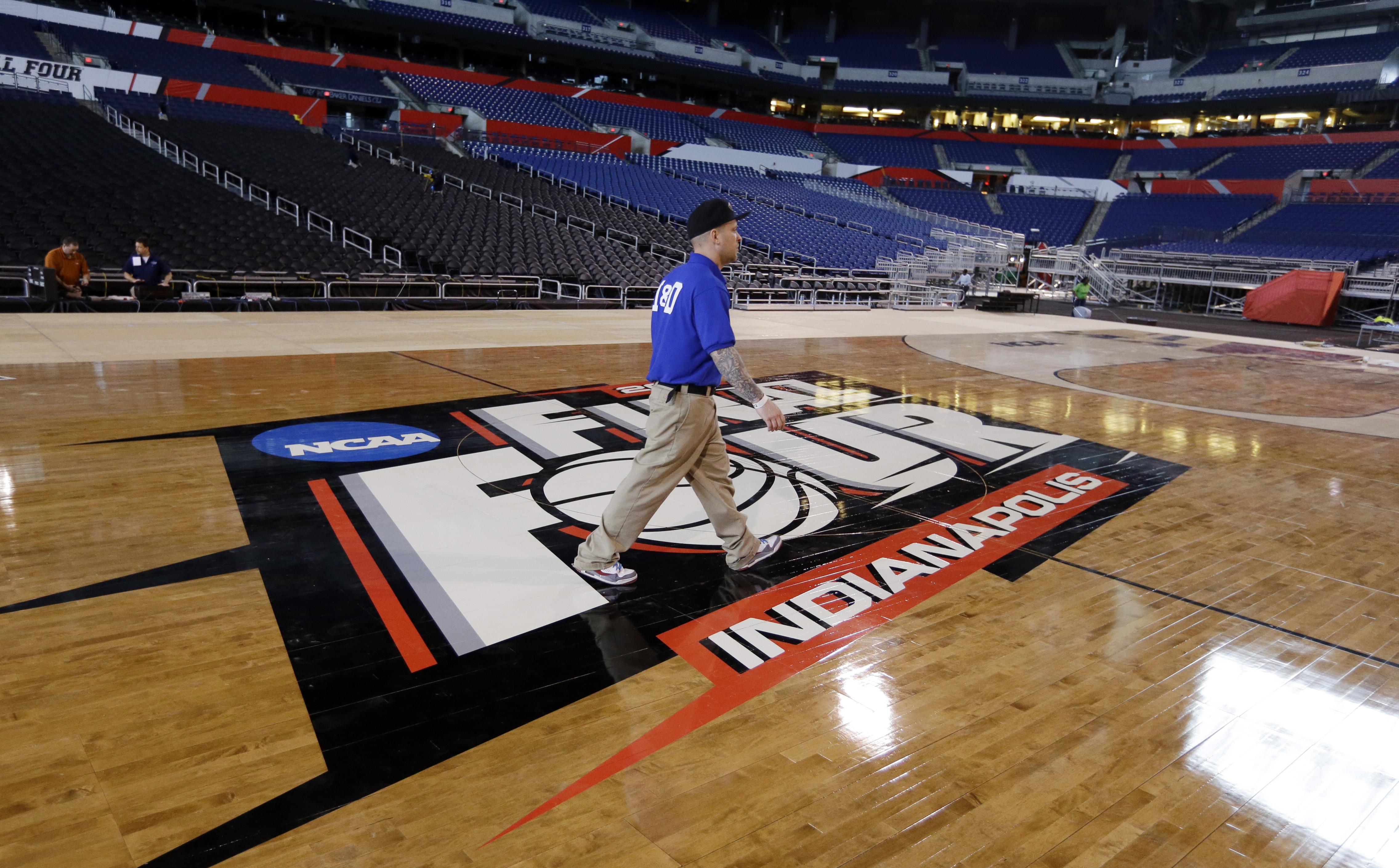 A worker crosses the Logo at center court as workers at Lucas Oil Stadium install the court in Indianapolis, Friday, March 27, 2015, as they prepare to host the NCAA Final Four college basketball games on April 4 and 6. (AP Photo/Michael Conroy)