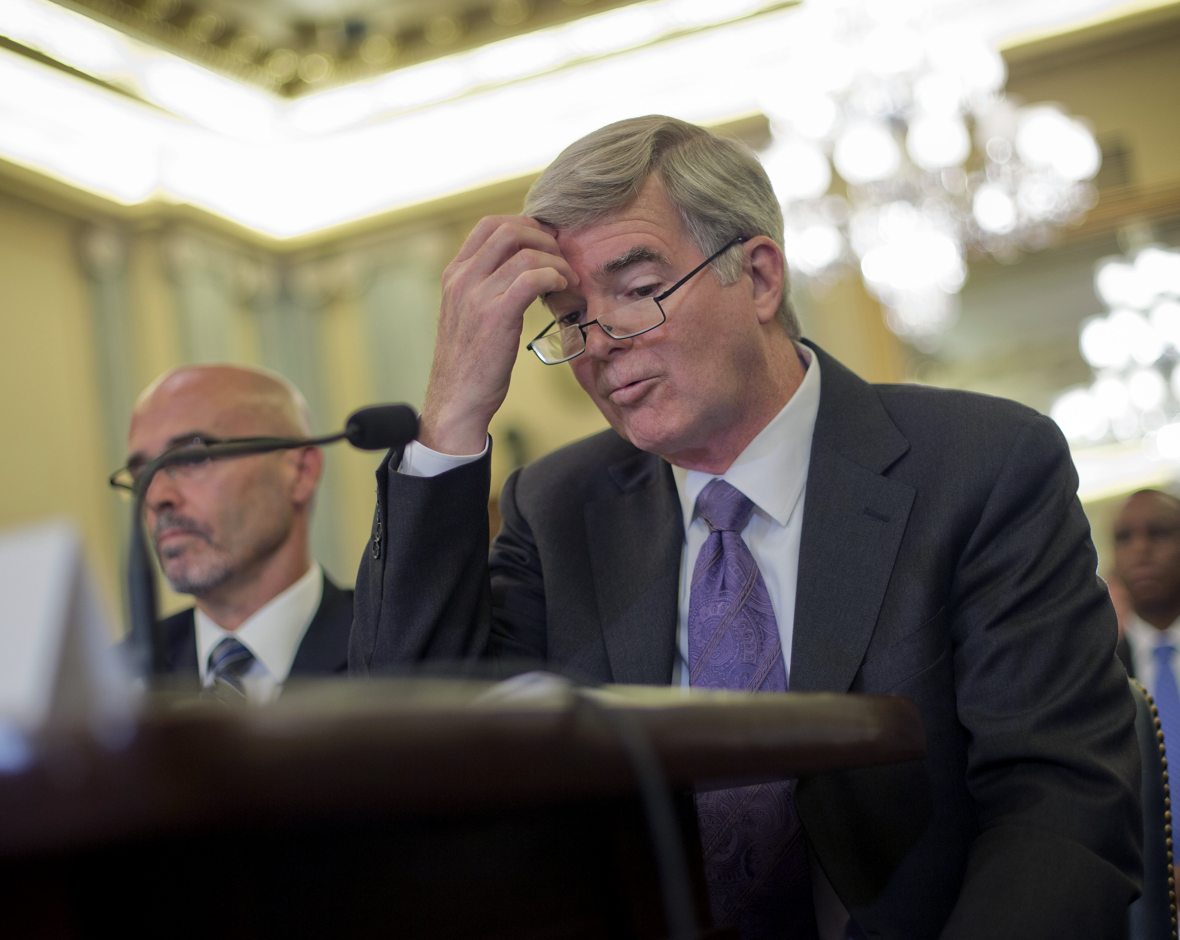 FILE - In this July 9, 2014, file photo, NCAA President Mark Emmert scratches his forehead as he testifies on Capitol Hill in Washington before the Senate Commerce, Science and Transportation hearing on the NCAA's treatment of athletes. At left is Dr. Ric