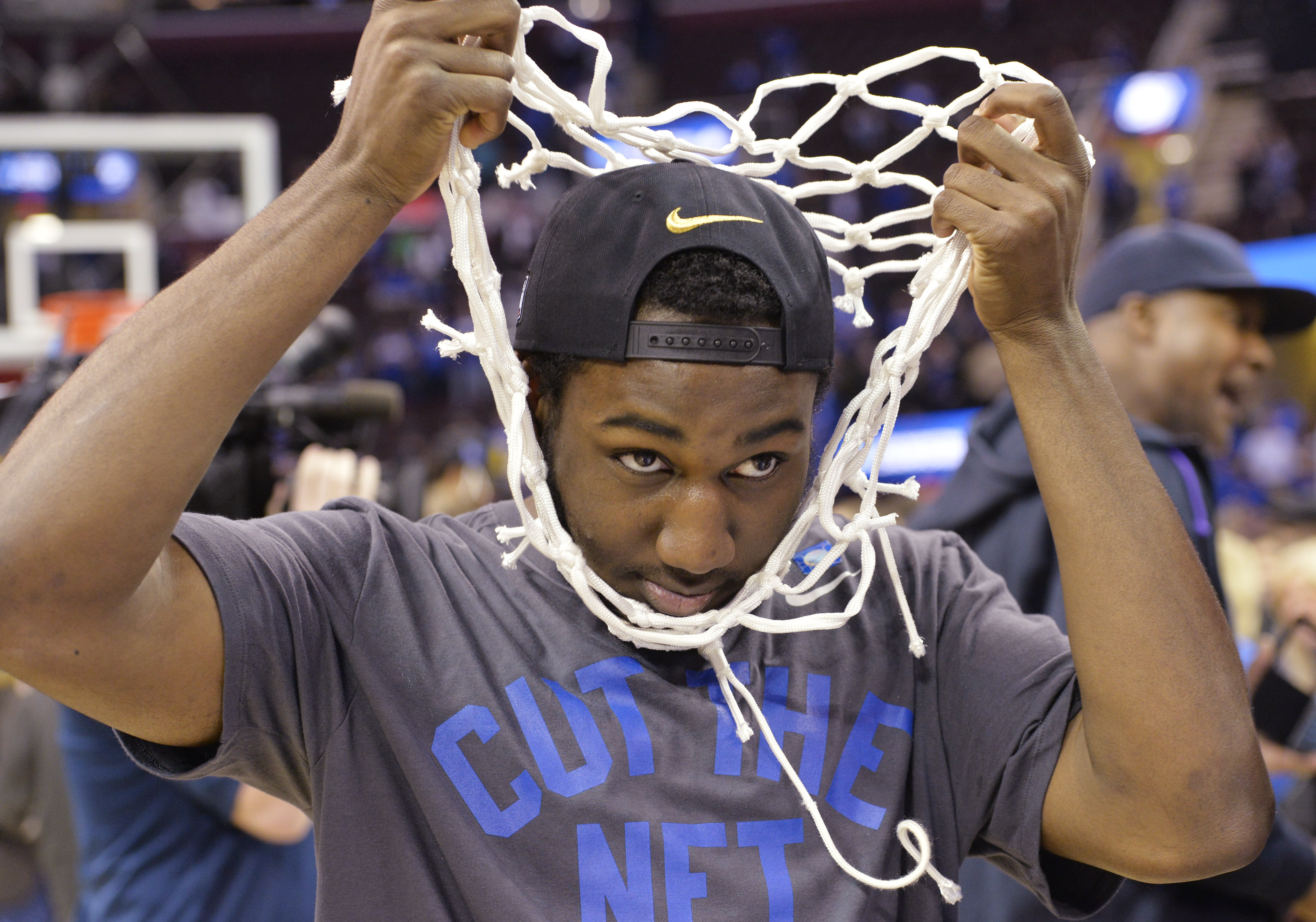 Kentucky's Dominique Hawkins pulls the net over his head during the celebration after Kentucky's 68-66 win over Notre Dame in a college basketball game in the NCAA men's tournament regional finals, Saturday, March 28, 2015, in Cleveland. Kentucky remains