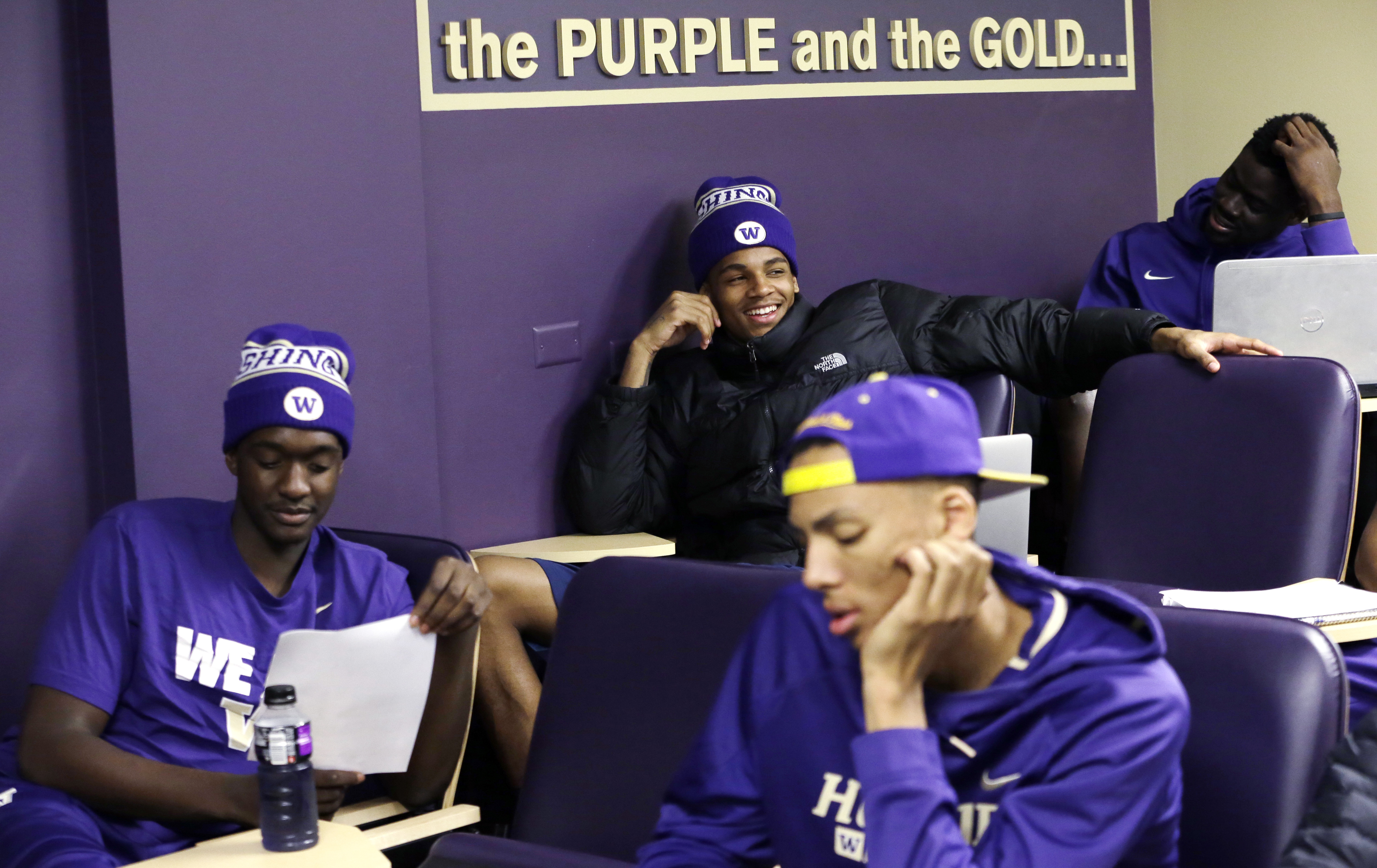 In this photo taken Sept. 28, 2015, Washington men's basketball player Dejounte Murray, center back, smiles as he comments during a class in Chinese culture in Seattle. Washington is embarking on a unique journey to begin the 2015-16 basketball season. Th