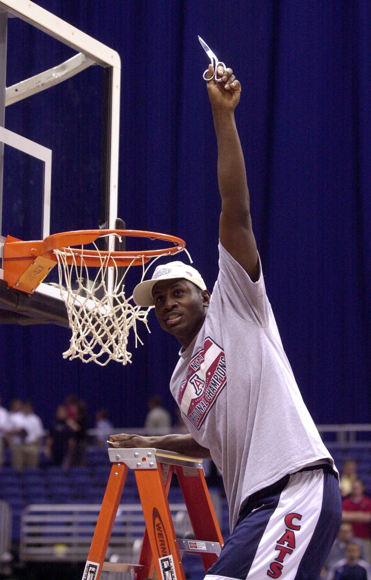 Arizona's Michael Wright looks to the stands after cutting his share of the net following Arizona's 87-81 win over Illinois in the NCAA Midwest Regional final Sunday, March 25, 2001, at the Alamodome in San Antonio. (AP Photo/Eric Gay)