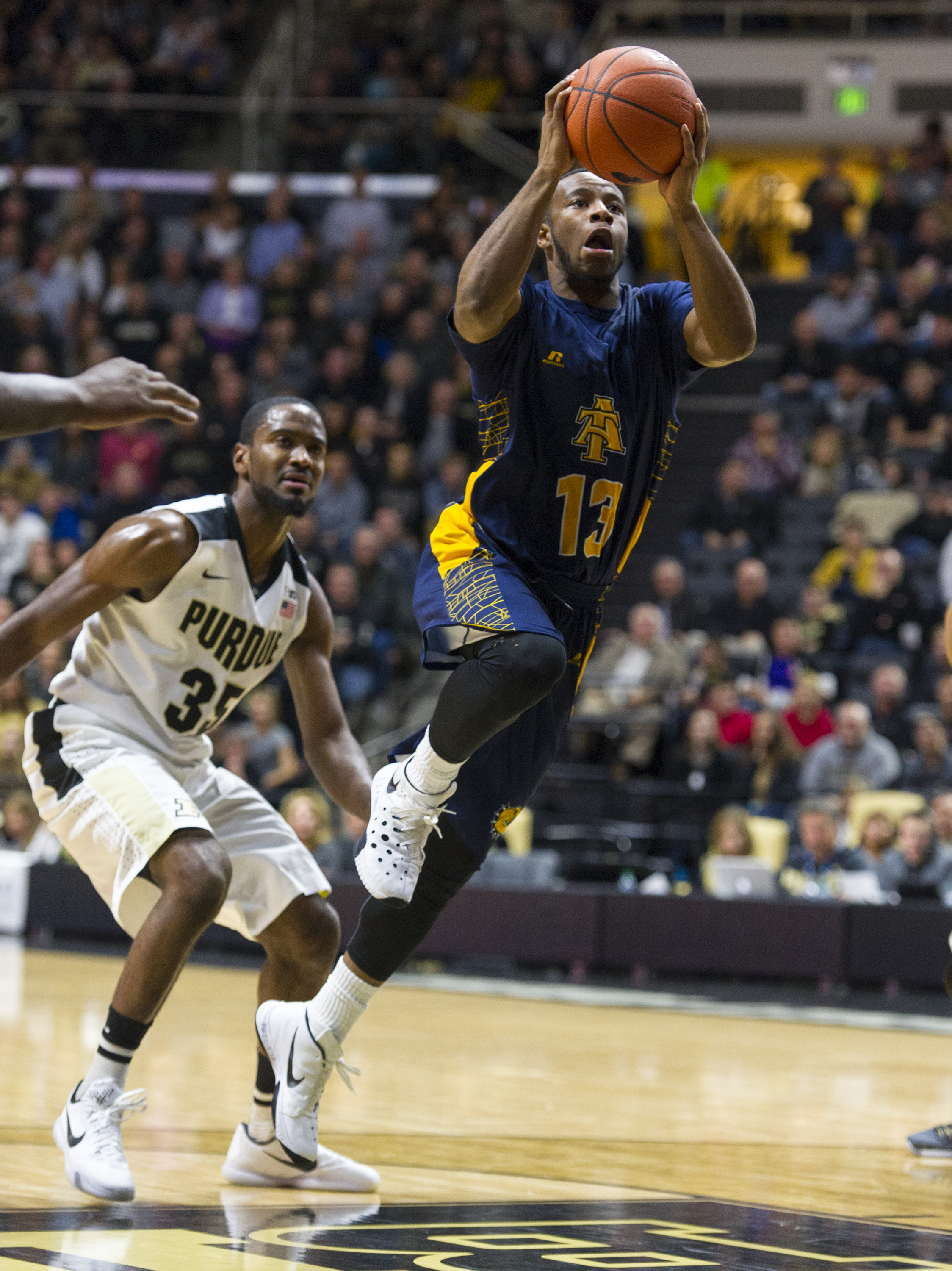 North Carolina A&T guard Austin Williams (13) races past Purdue guard Rapheal Davis (35) in an effort to get off a last-second shot to end the first half of an NCAA college basketball game, Friday, Nov. 13, 2015, in West Lafayette, Ind. (AP Photo/Doug McS