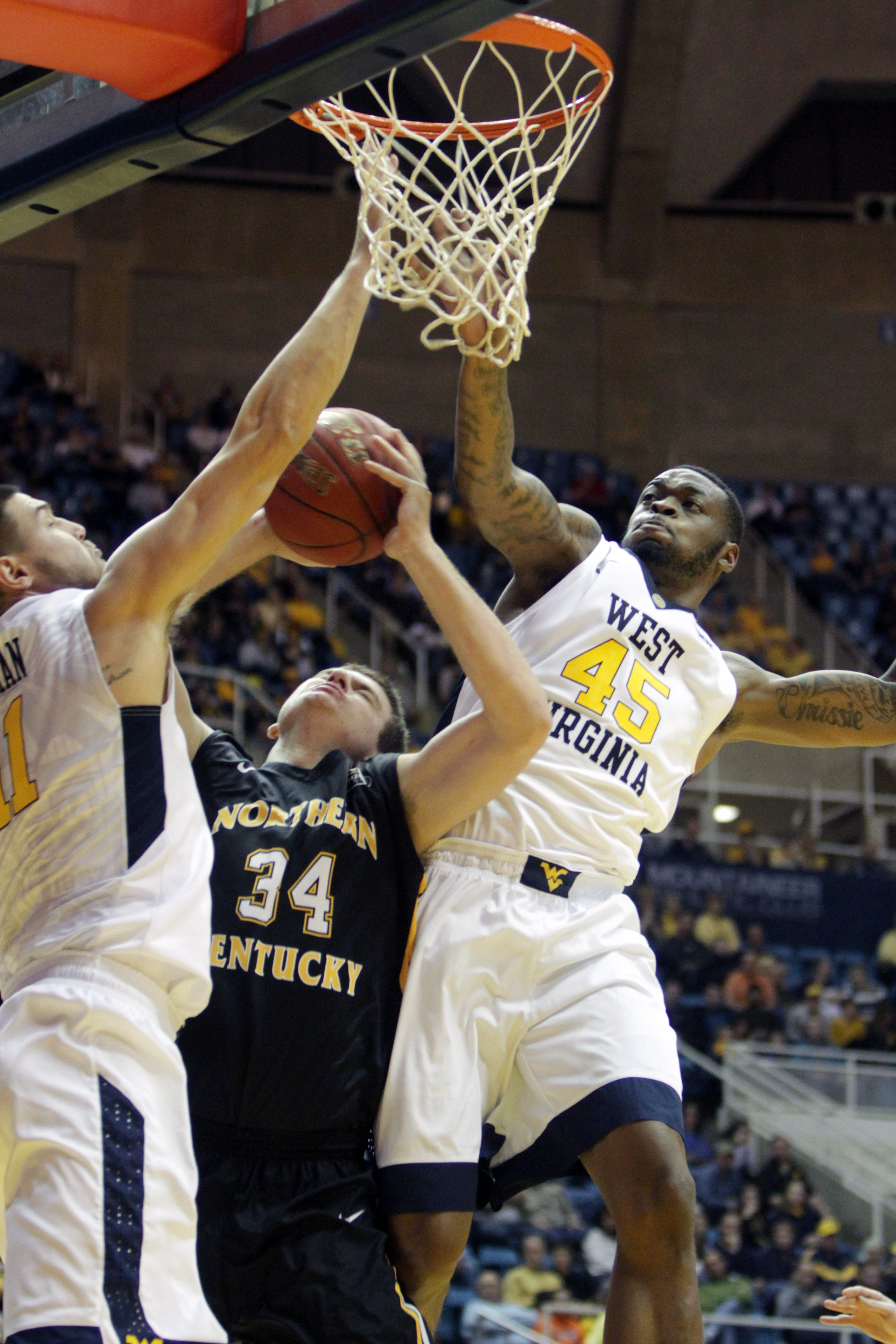 West Virginia forward Elijah Macon (45) blocks Northern Kentucky center Drew McDonald (34) shot during the first half of an NCAA college basketball game, Friday, Nov, 13, 2015, in Morgantown, W.Va. (AP Photo/Raymond Thompson)