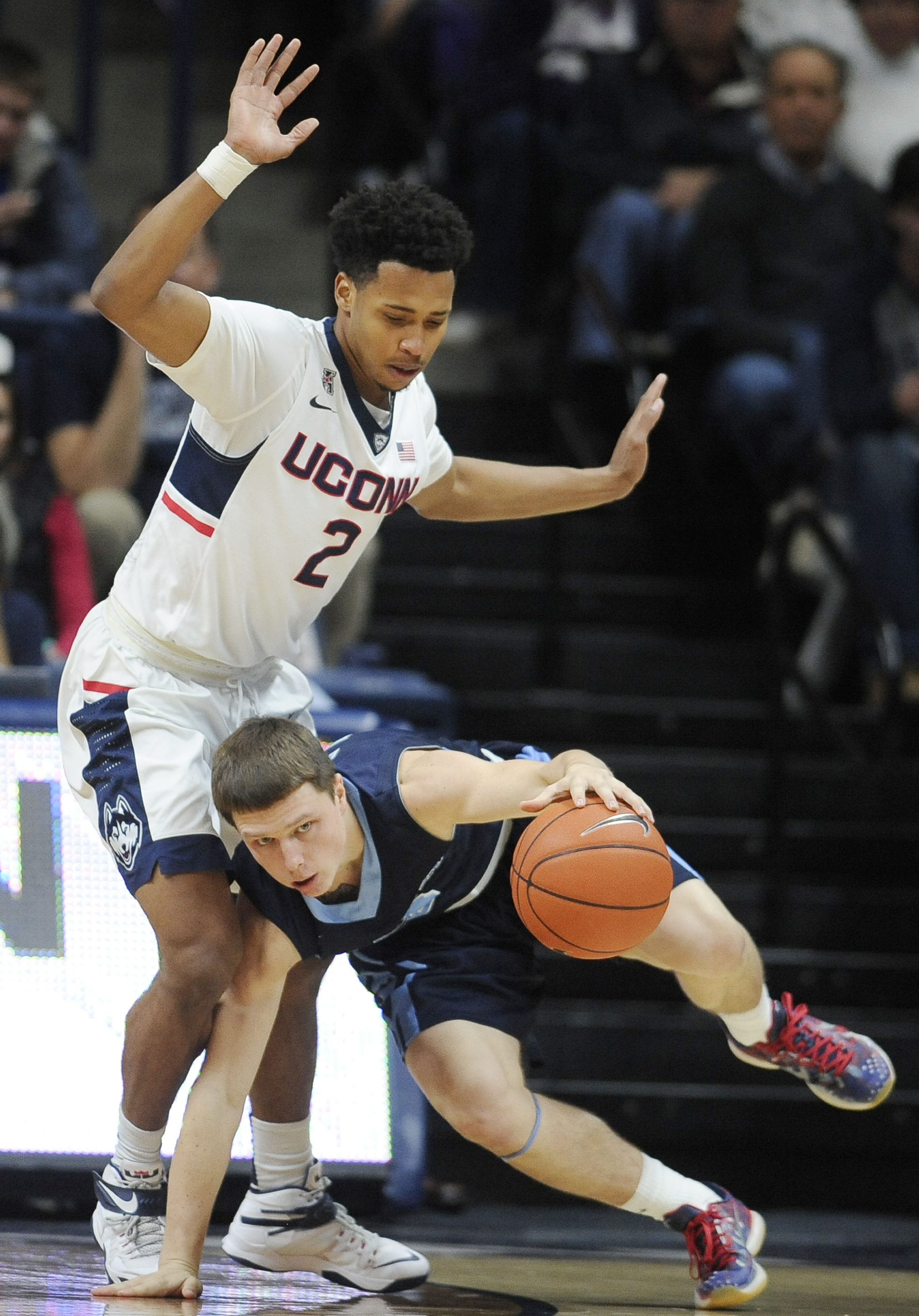 Maine's Christian Ejiga, right, stumbles while dribbling around Connecticut's Jalen Adams during the first half of an NCAA college basketball game, Friday, Nov. 13, 2015, in Storrs, Conn. (AP Photo/Jessica Hill)
