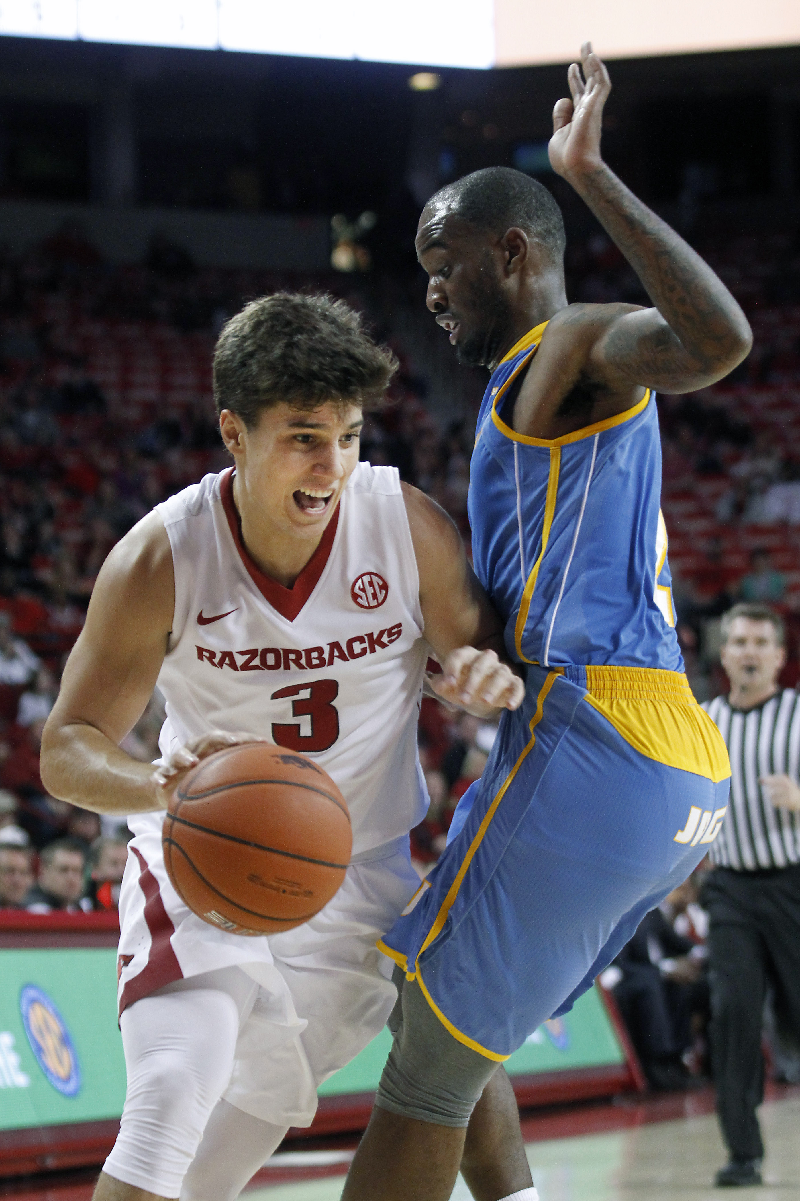 Arkansas' Dusty Hannahs (3) moves past Southern University's Adrian Rodgers during the first half of an NCAA college basketball game Friday, Nov. 13, 2015, in Fayetteville, Ark. (AP Photo/Samantha Baker)