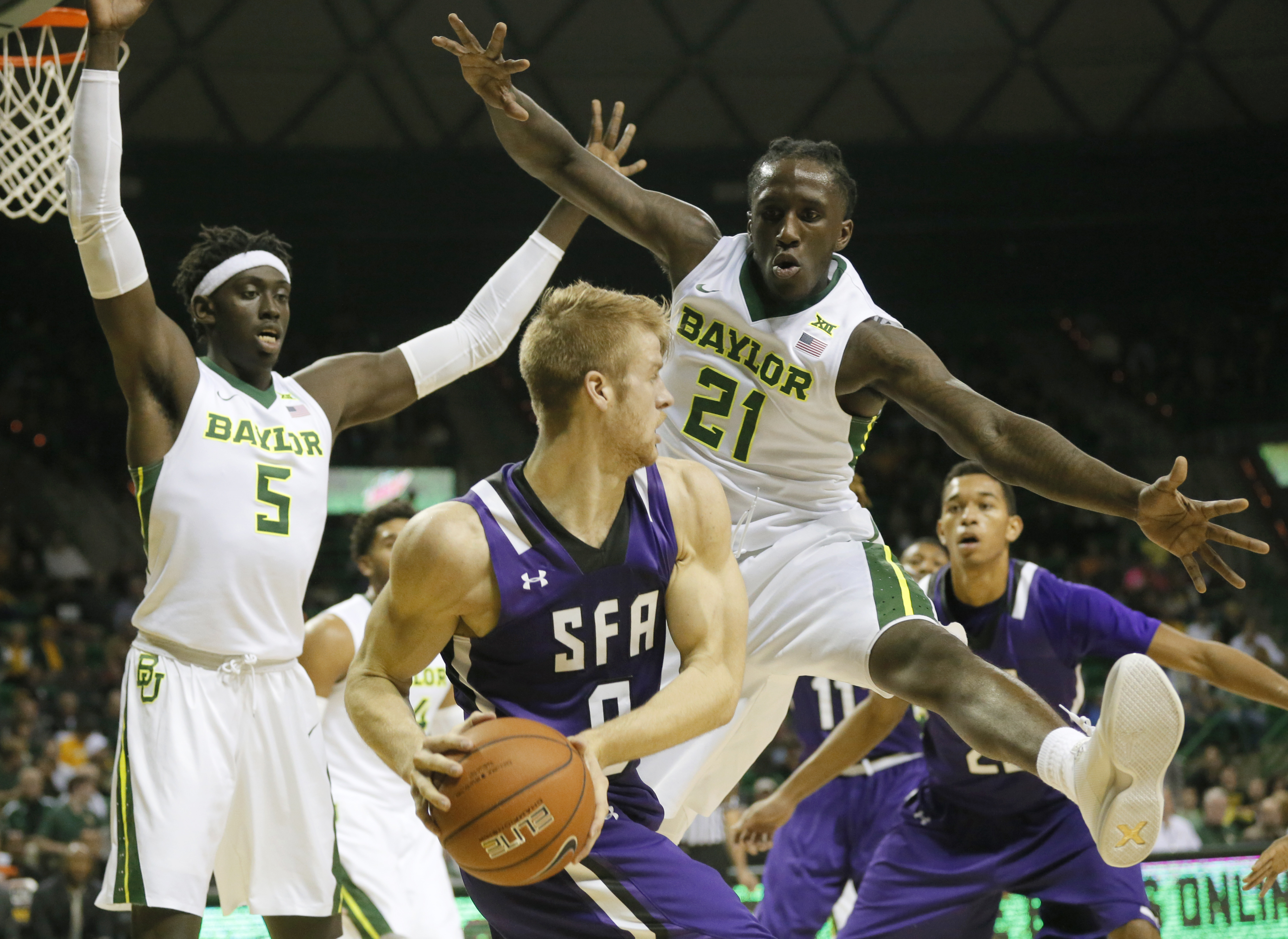 Stephen F. Austin's Thomas Walkup (0) attempts to make a pass as Baylor's Johnathan Motley (5) and Taurean Prince (21) defend in the first half of an NCAA college basketball game Friday, Nov. 13, 2015, in Waco, Texas. (AP Photo/Tony Gutierrez)