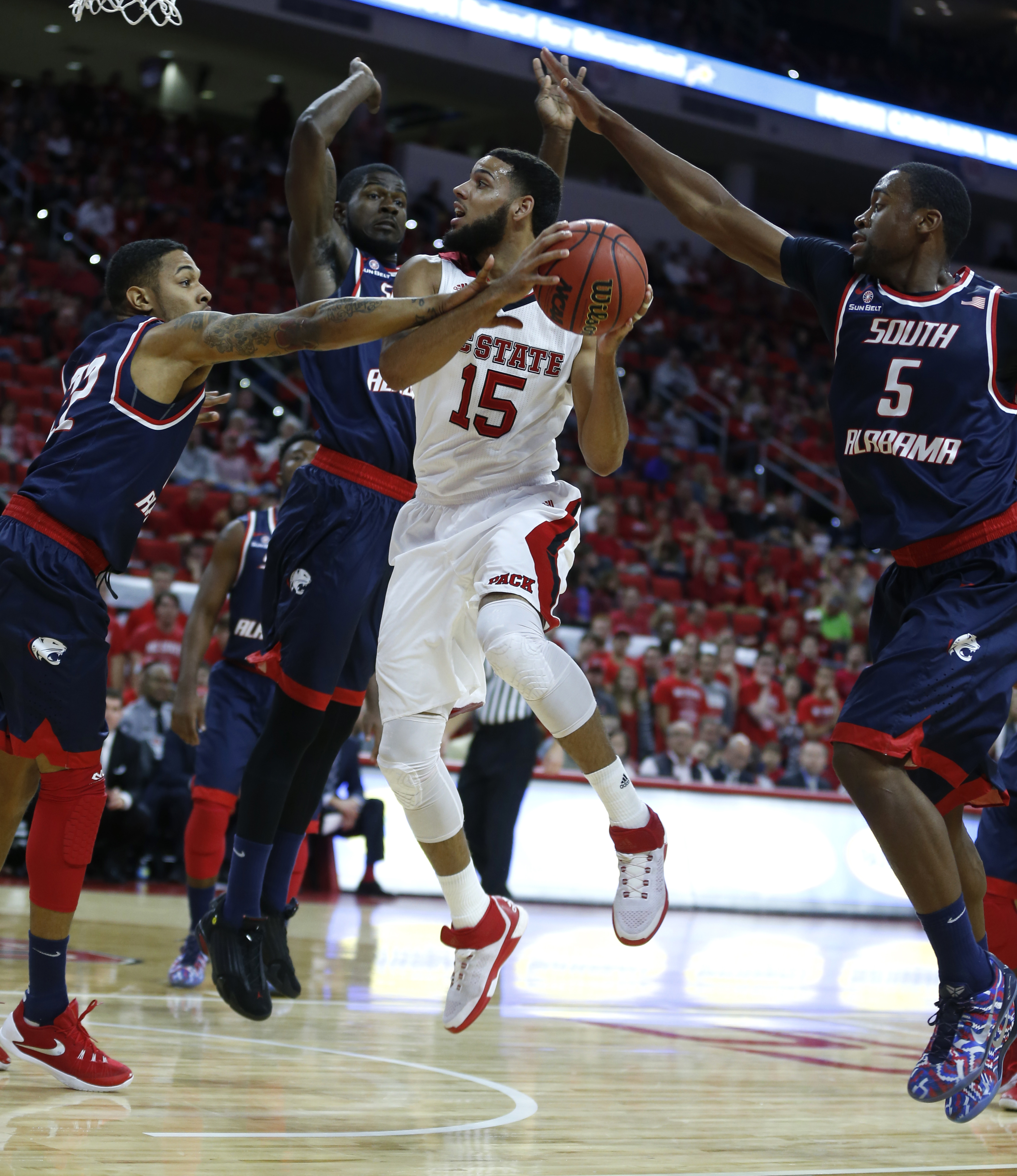 South Alabama's John Brown (22), left, Tafari Whittingham, center left, and Don MuepoKelly (5) defend against North Carolina State's Cody Martin (15) during the first half of an NCAA college basketball game in Raleigh, N.C., Sunday, Nov. 15, 2015. (Ethan
