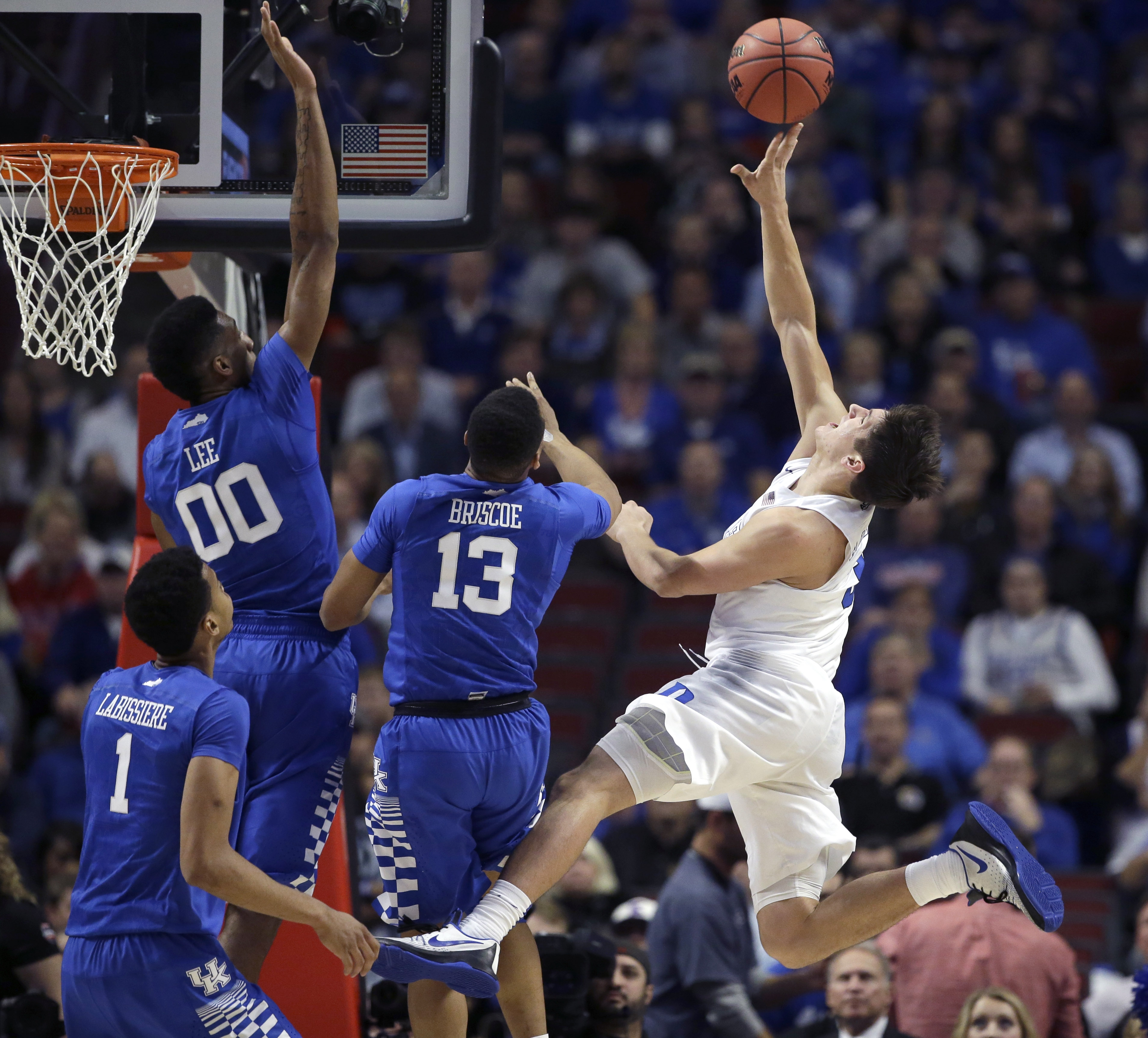 Duke guard Grayson Allen, left, shoots off balance over Kentucky forward Skal Labissiere (1) Marcus Lee (00) and Isaiah Briscoe, during the first half of an NCAA basketball game, Tuesday, Nov. 17, 2015, in Chicago. (AP Photo/Nam Y. Huh)