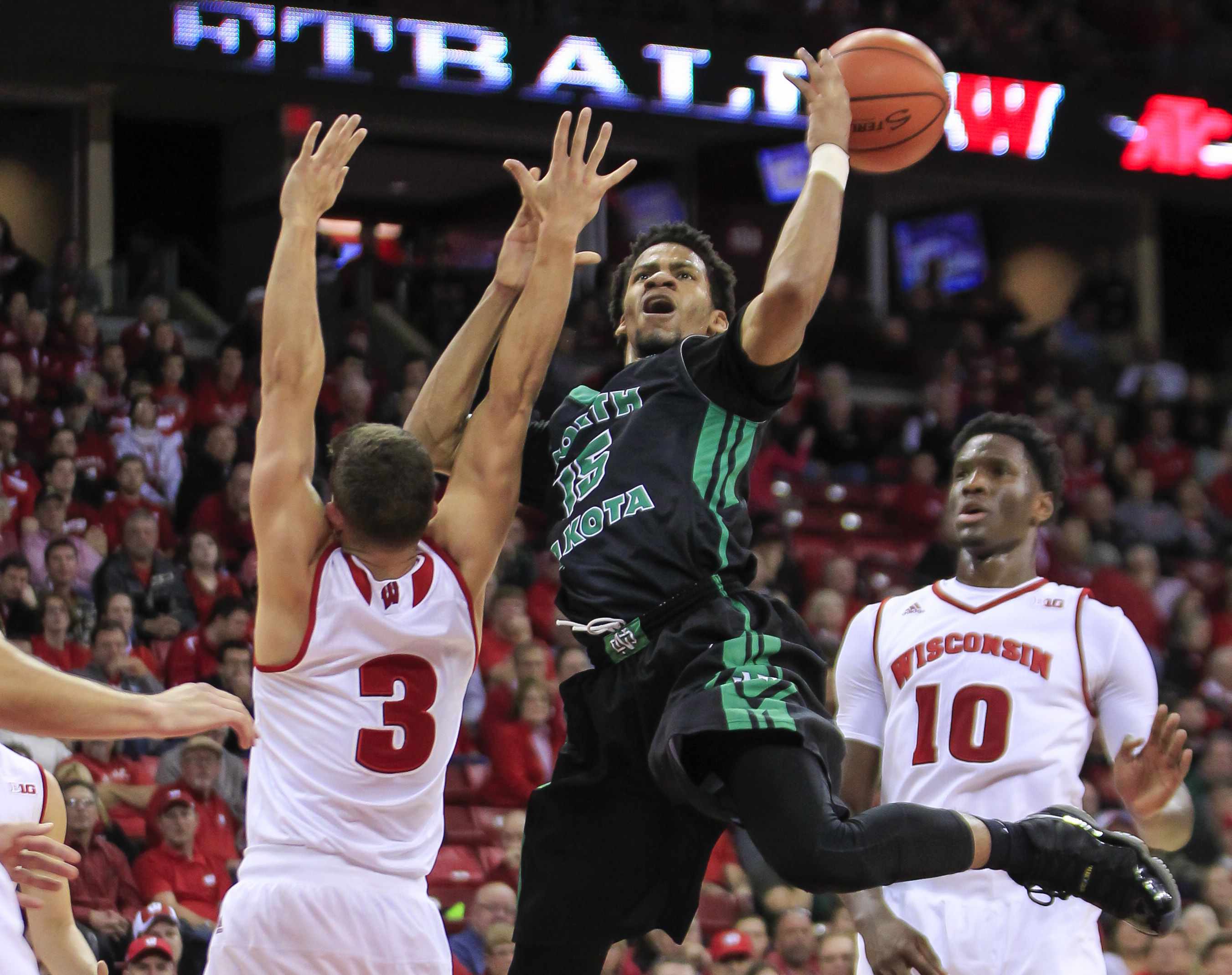 Wisconsin's Zak Showalter (3) blocks a shot by North Dakota's Cortez Seales (15) during the first half of an NCAA college basketball game Tuesday, Nov. 17, 2015, in Madison, Wis. (AP Photo/Andy Manis)