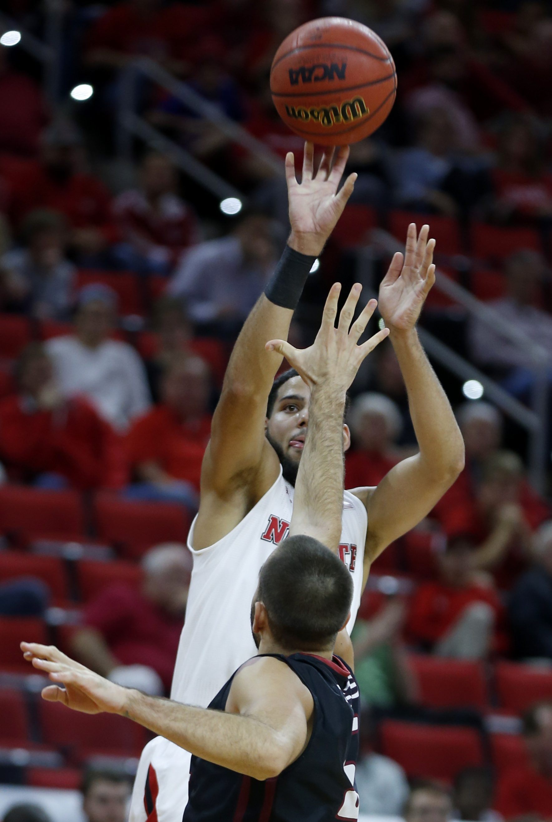 N.C. State's Caleb Martin (14) shoots as IUPUI's Leo Svete (5) defends during the first half of an NCAA college basketball game at PNC Arena in Raleigh, N.C., Wednesday, Nov. 18, 2015.  (Ethan Hyman/The News & Observer via AP)