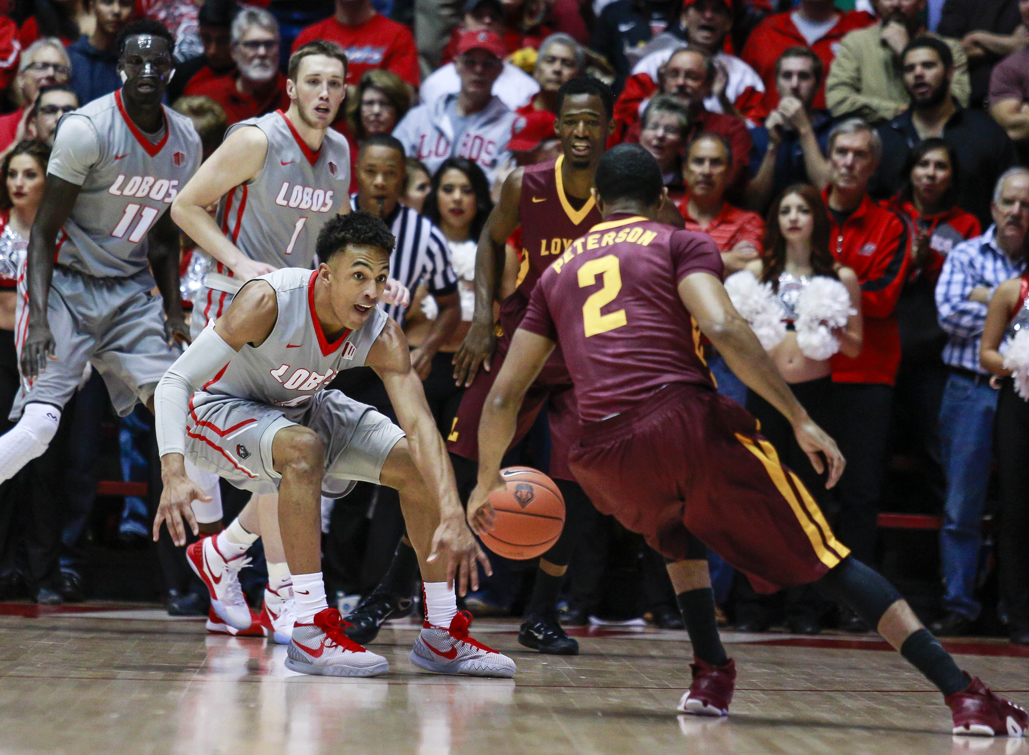 New Mexico's Elijah Brown (4) Cullen Neal (1) and Obij Aget (11) guard Loyola Chicago's Earl Peterson (2) during the first half of an NCAA college basketball game, Wednesday, Nov. 18, 2015, in Albuquerque, N.M. (AP Photo/Juan Labreche)