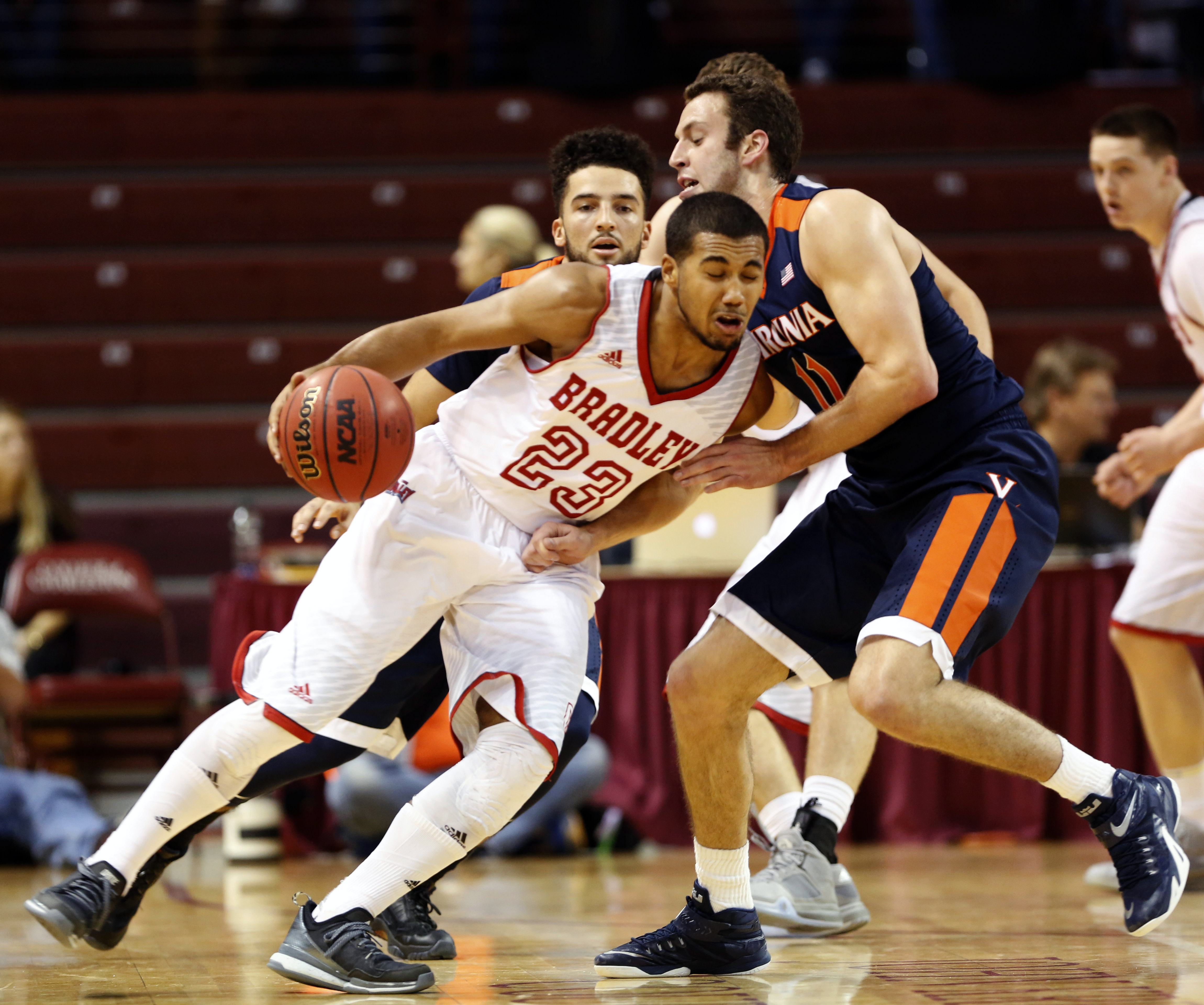 Virginia's Evan Nolte, right, gets run over by Bradley's Dwayne Lautier-Ogunleye during the first half of an NCAA college basketball game at the Charleston Classic at TD Arena, Thursday Nov. 19, 2015, in Charleston, S.C.  (AP Photo/Mic Smith)