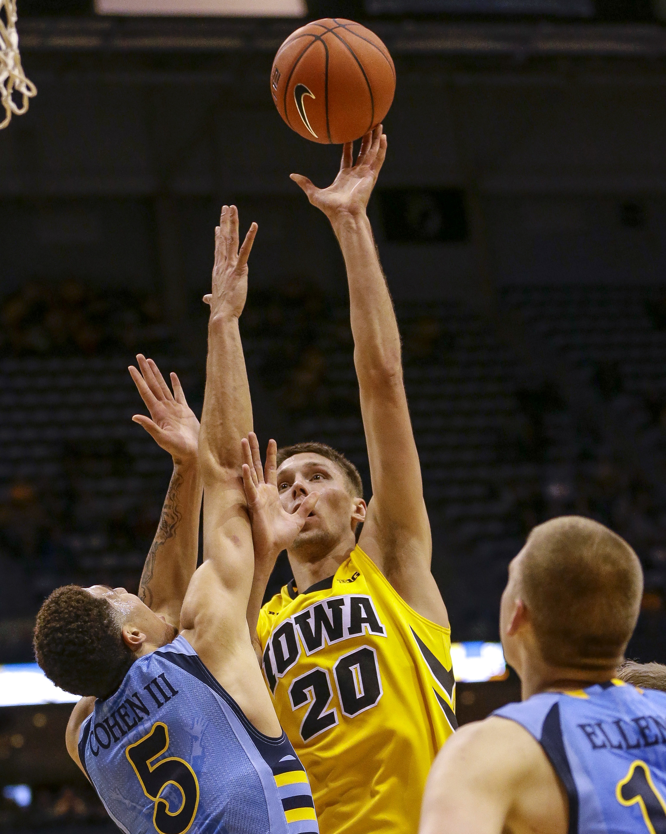 Marquette's Sandy Cohen III defends Iowa's Jarrod Uthoff as he shoots during the second half of an NCAA college basketball game Thursday, Nov. 19, 2015, in Milwaukee. (AP Photo/Tom Lynn)