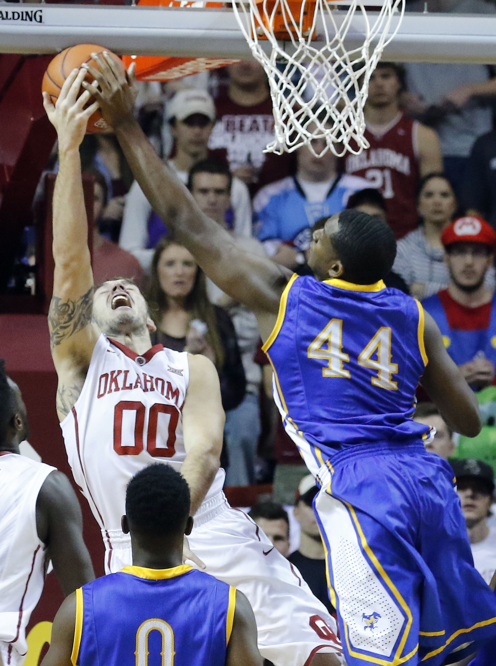 Oklahoma forward Ryan Spangler (00) goes up for a basket as McNeese State forward Austin Lewis (44) defends during the first half of an NCAA mens basketball game in Norman, Okla., Friday, Nov. 20, 2015. (AP Photo/Alonzo Adams)