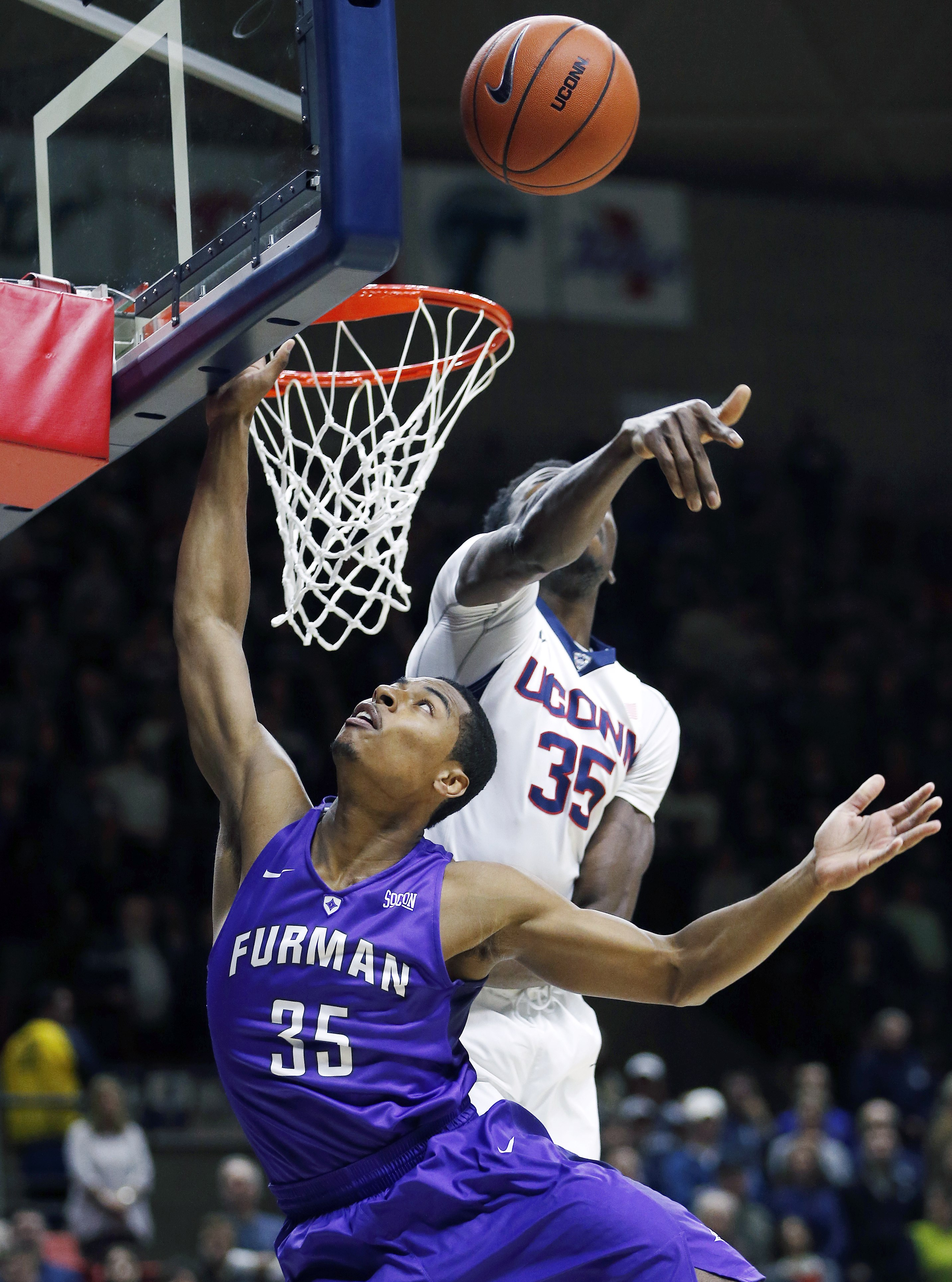 Connecticut's Amida Brimah, top, blocks a shot by Furman's Daniel Fowler during the first half of an NCAA college basketball game in Storrs, Conn., Saturday, Nov. 21, 2015. (AP Photo/Michael Dwyer)