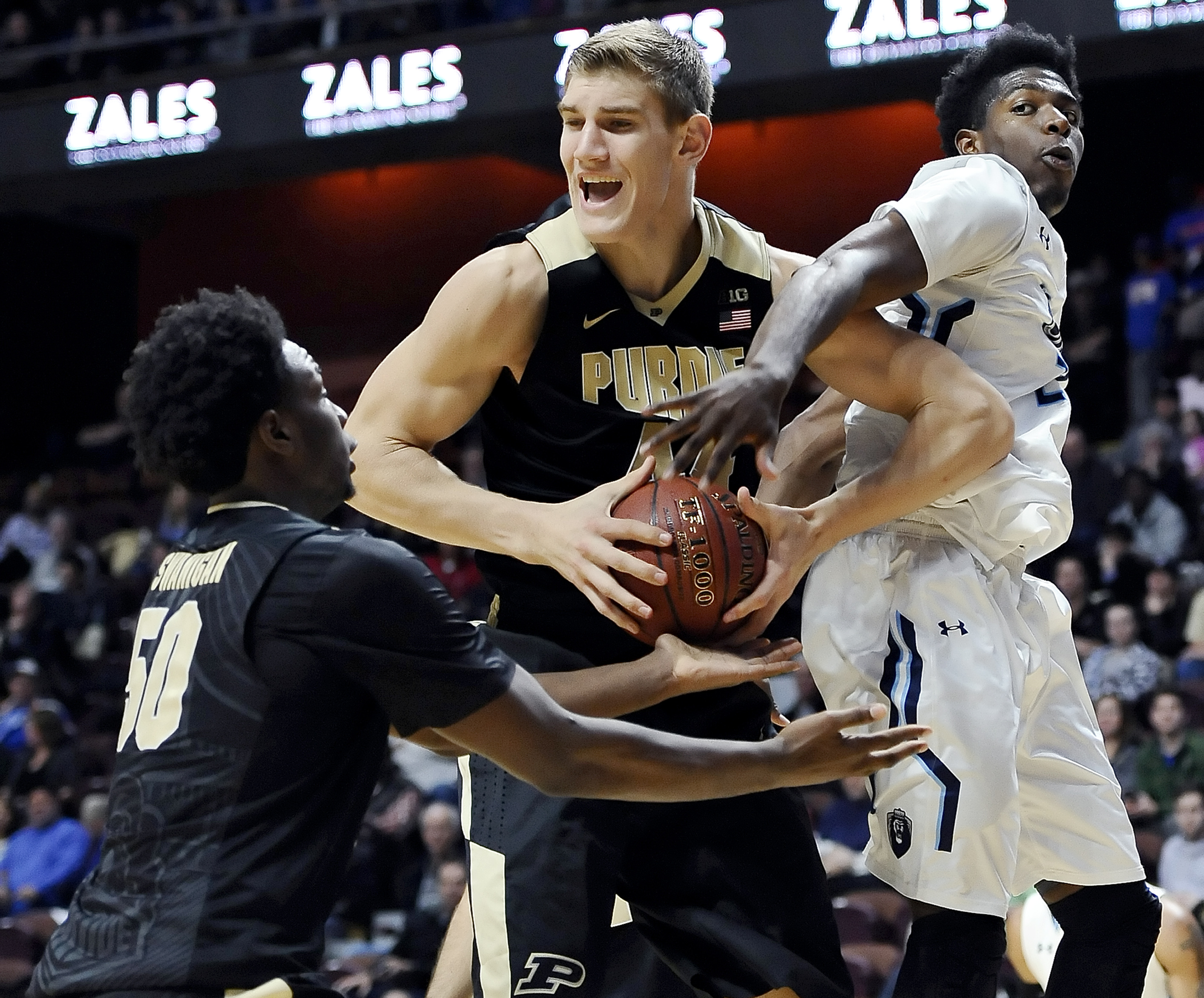 Purdue's Isaac Haas, center, looks to teammate Caleb Swanigan, left, as he brings down a rebound against Old Dominion's Denzell Taylor, right, during the second half of an NCAA college basketball game in the Hall of Fame Tip-Off tournament, Saturday, Nov.