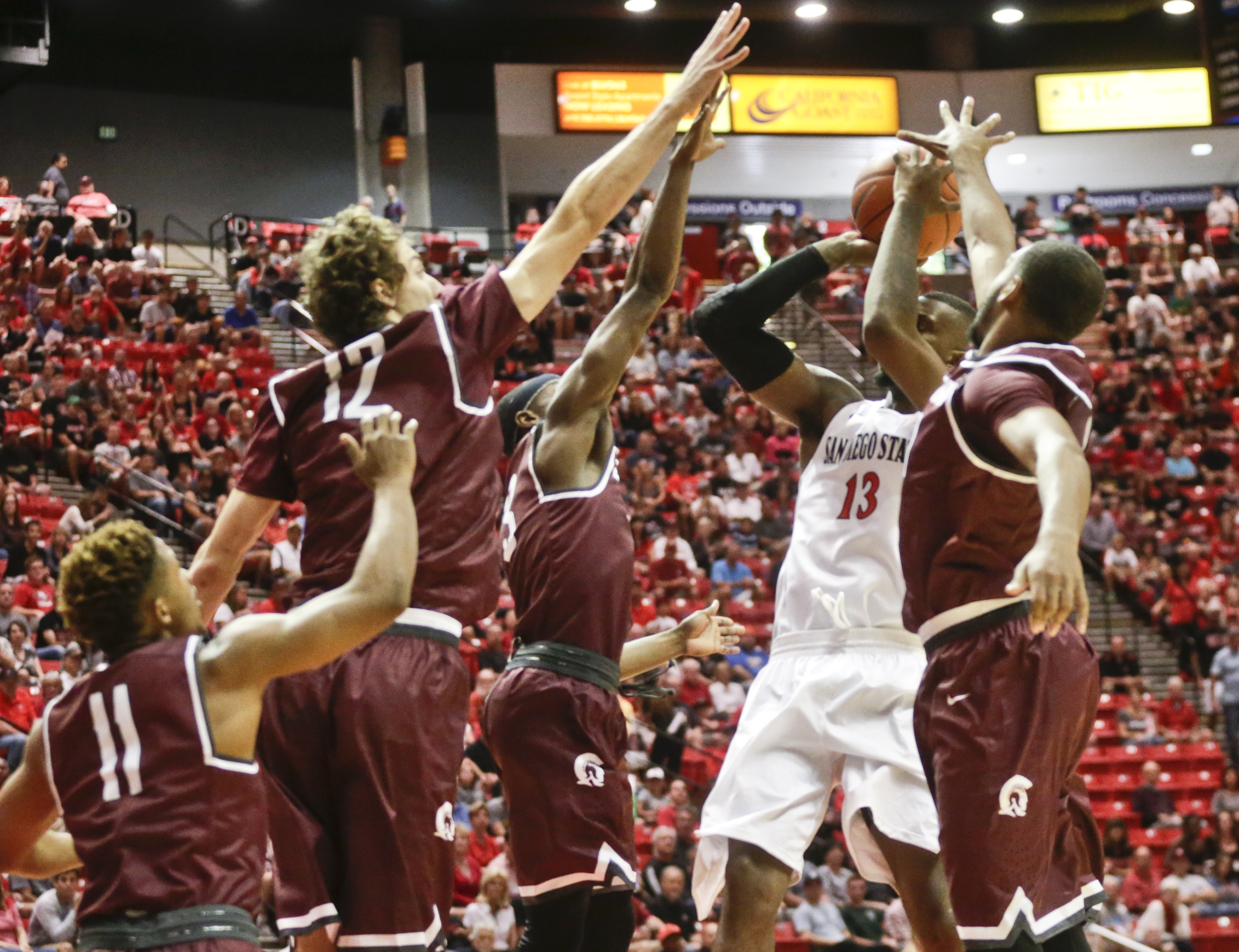 San Diego State forward Winston Shepard (13) has his shot blocked as he swarmed by four Arkansas-Little Rock defenders in the first half of an NCAA college basketball game Saturday, Nov. 21, 2015, in San Diego. (AP Photo/Lenny Ignelzi)