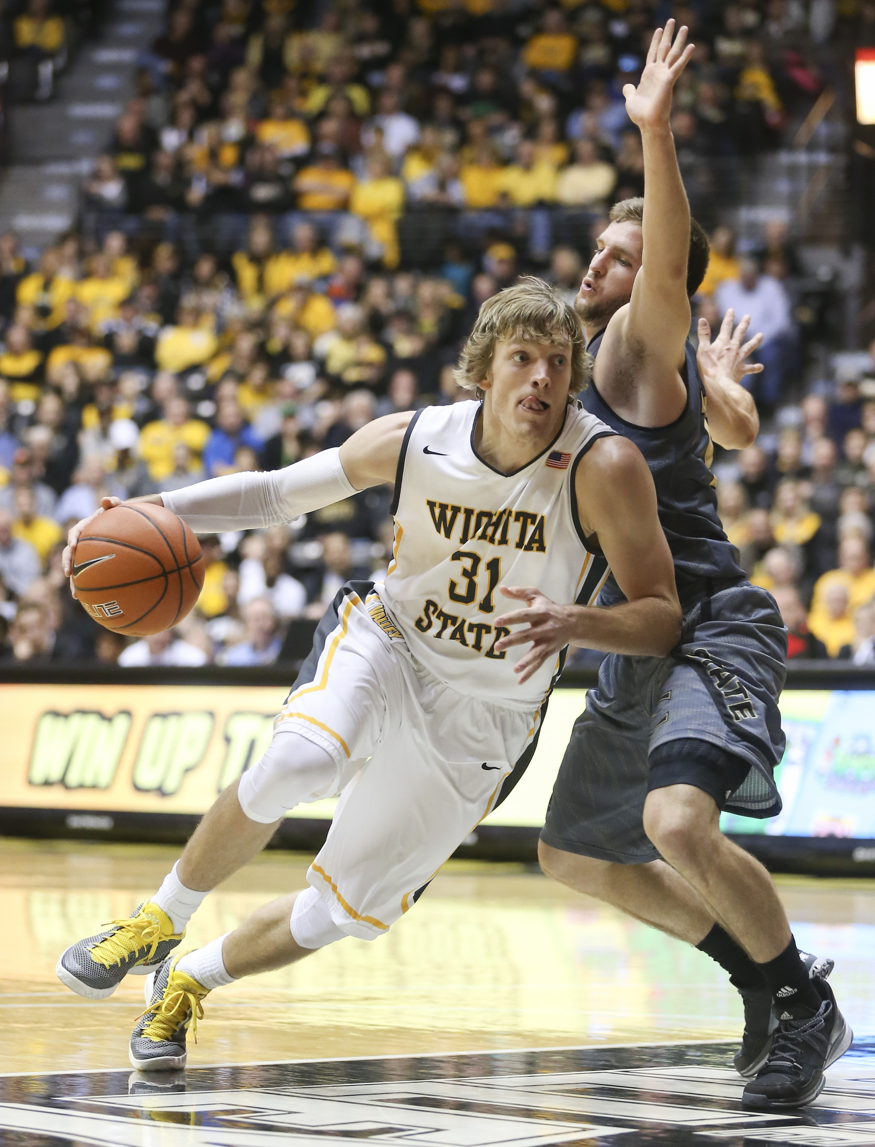 Wichita State guard Ron Baker drives to the basket against  Emporia State guard Micah Swank during the second half of an NCAA college basketball game in Wichita, Kan., on Saturday, Nov. 21, 2015. (Travis Heying/The Wichita Eagle via AP)
