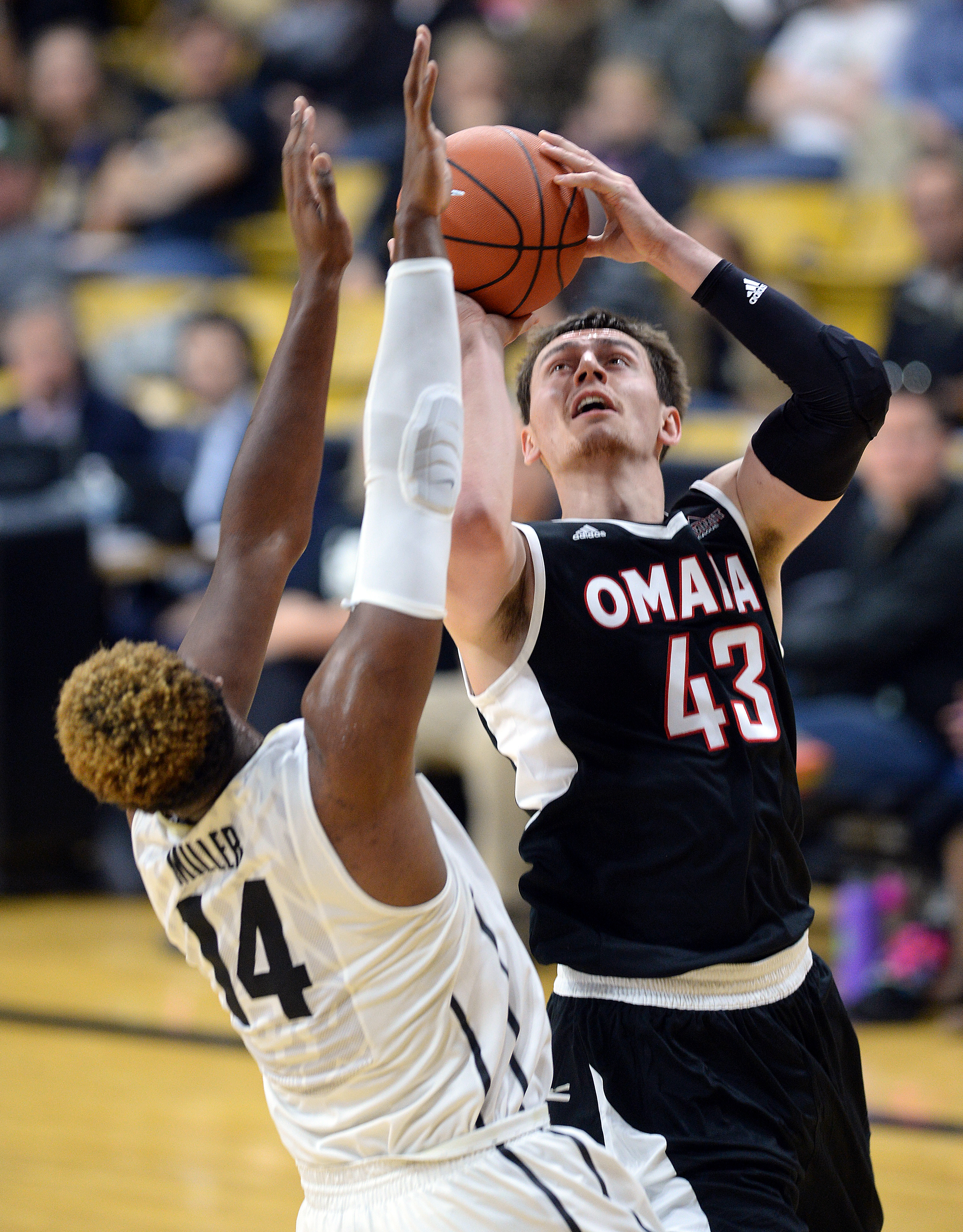 Nebraska-Omaha's Jake White shoots over Colorado's Tory Miller during the first half of an NCAA college basketball game Sunday, Nov. 22, 2015, in Boulder, Colo. (Cliff Grassmick/The Daily Camera via AP)