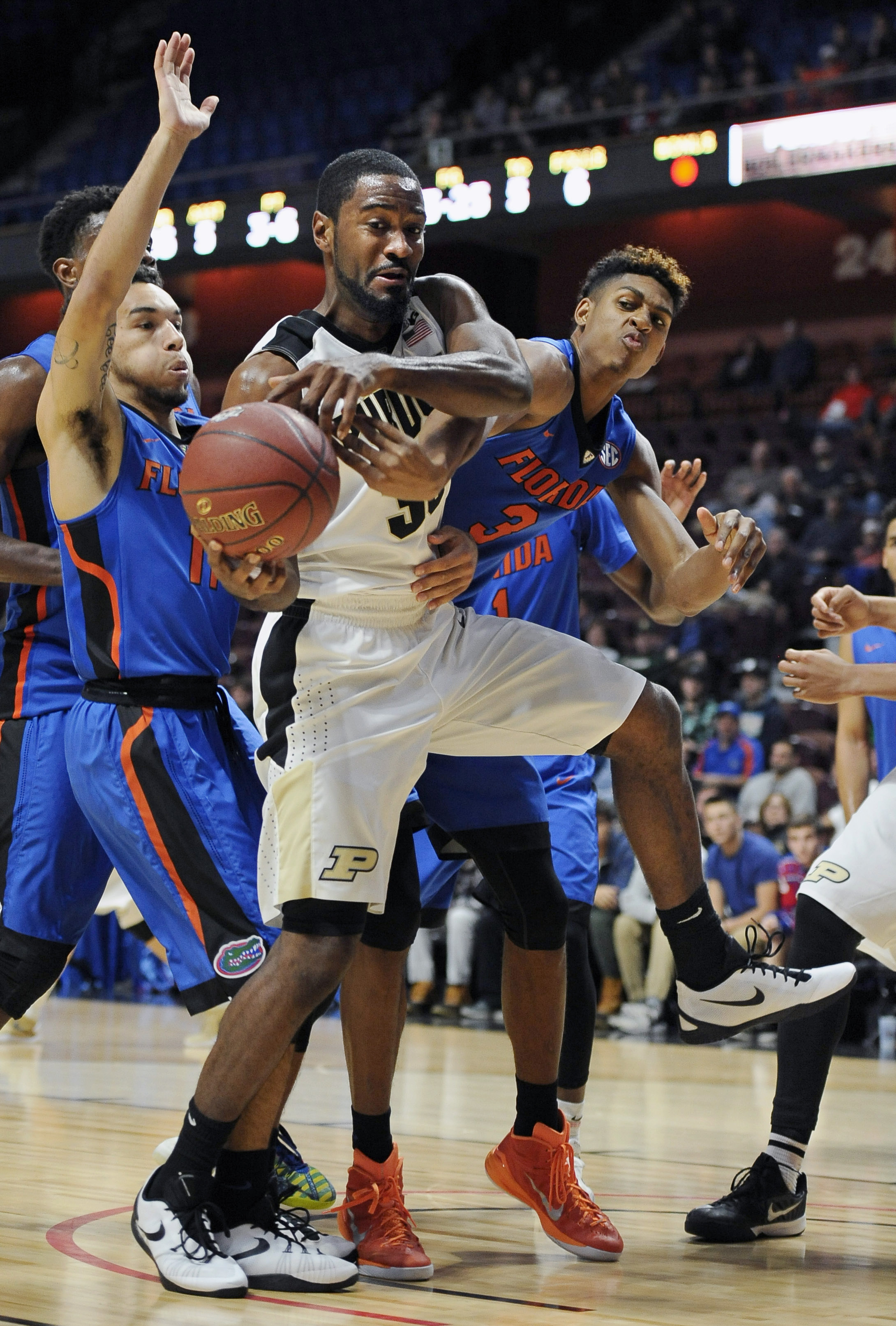 Purdue's Rapheal Davis, center, keeps the ball from Florida's Chris Chiozza, left, and Devin Robinson, right, during the first half of an NCAA college basketball game Sunday, Nov. 22, 2015, in Uncasville, Conn. (AP Photo/Jessica Hill)