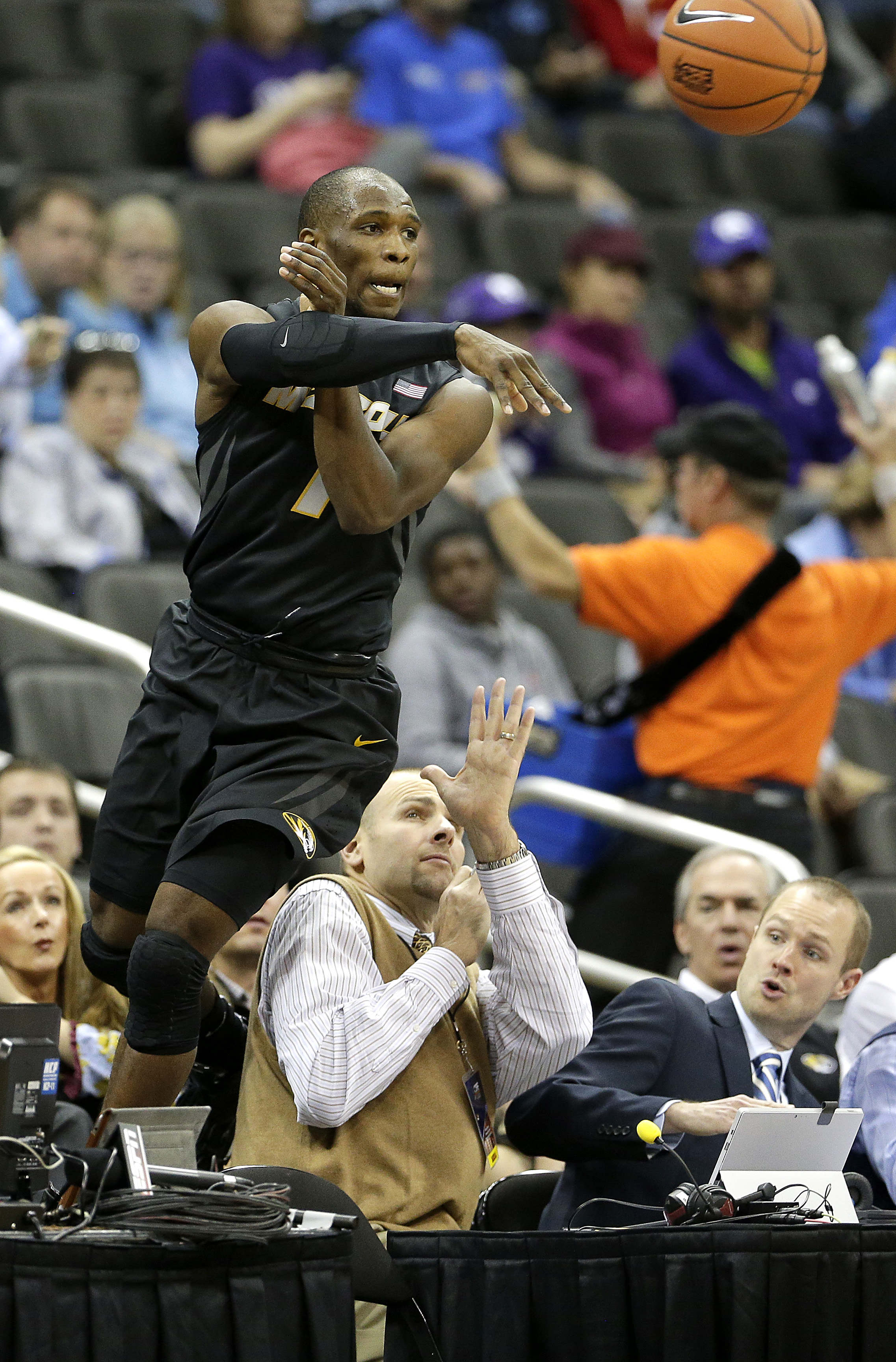 Missouri's Terrence Phillips leaps over the scorer's table as he attempts to keep a ball in bounds during the first half of an NCAA college basketball against Kansas State game Monday, Nov. 23, 2015 in Kansas City, Mo. (AP Photo/Charlie Riedel)