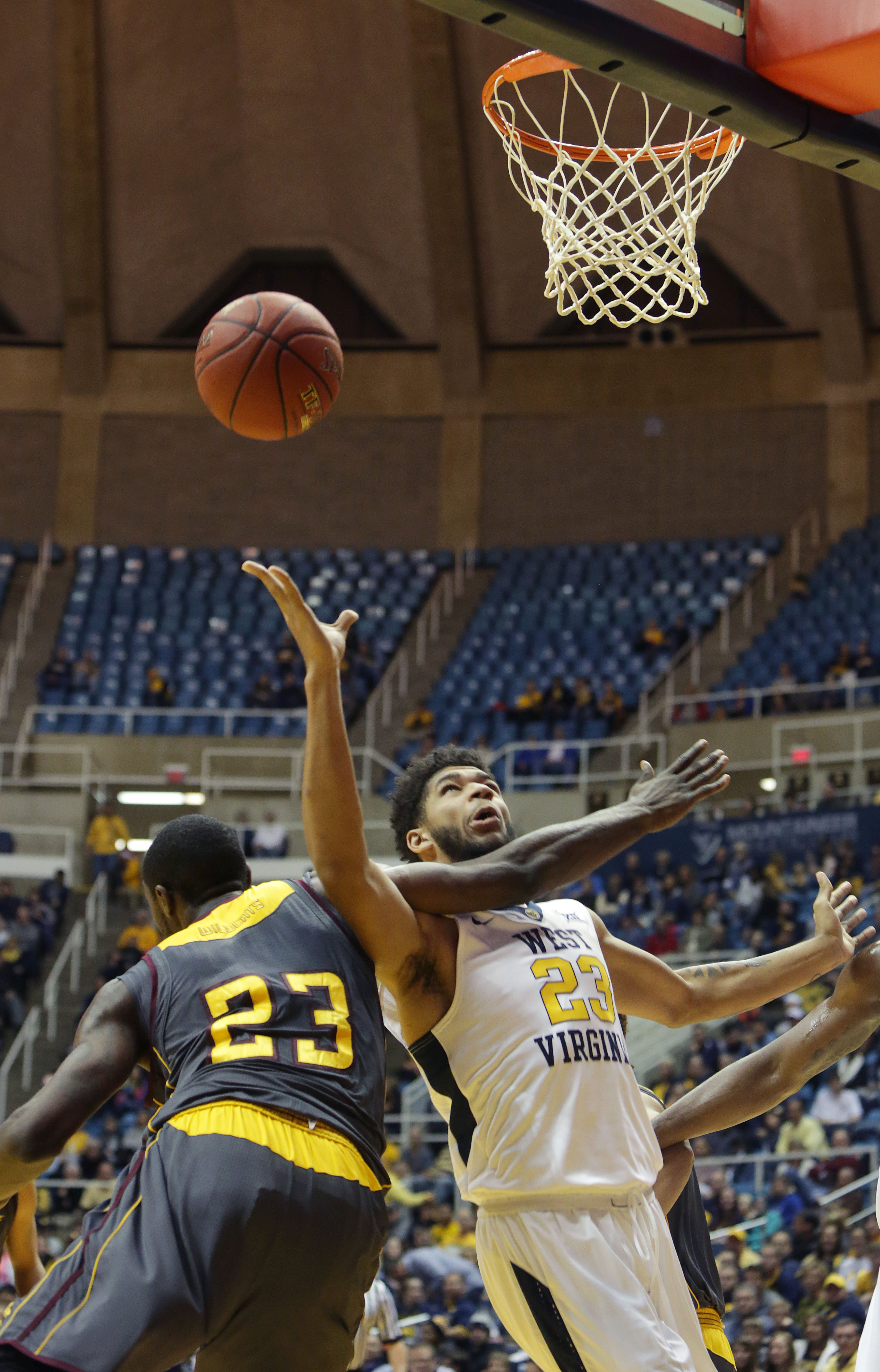 West Virginia forward Esa Ahmad (23) attempts a shot as Bethune-Cookman forward Mario Moody (23) goes for the block during the first half of an NCAA college basketball game Monday, Nov, 23, 2015, in Morgantown, W.Va. (AP Photo/Raymond Thompson)