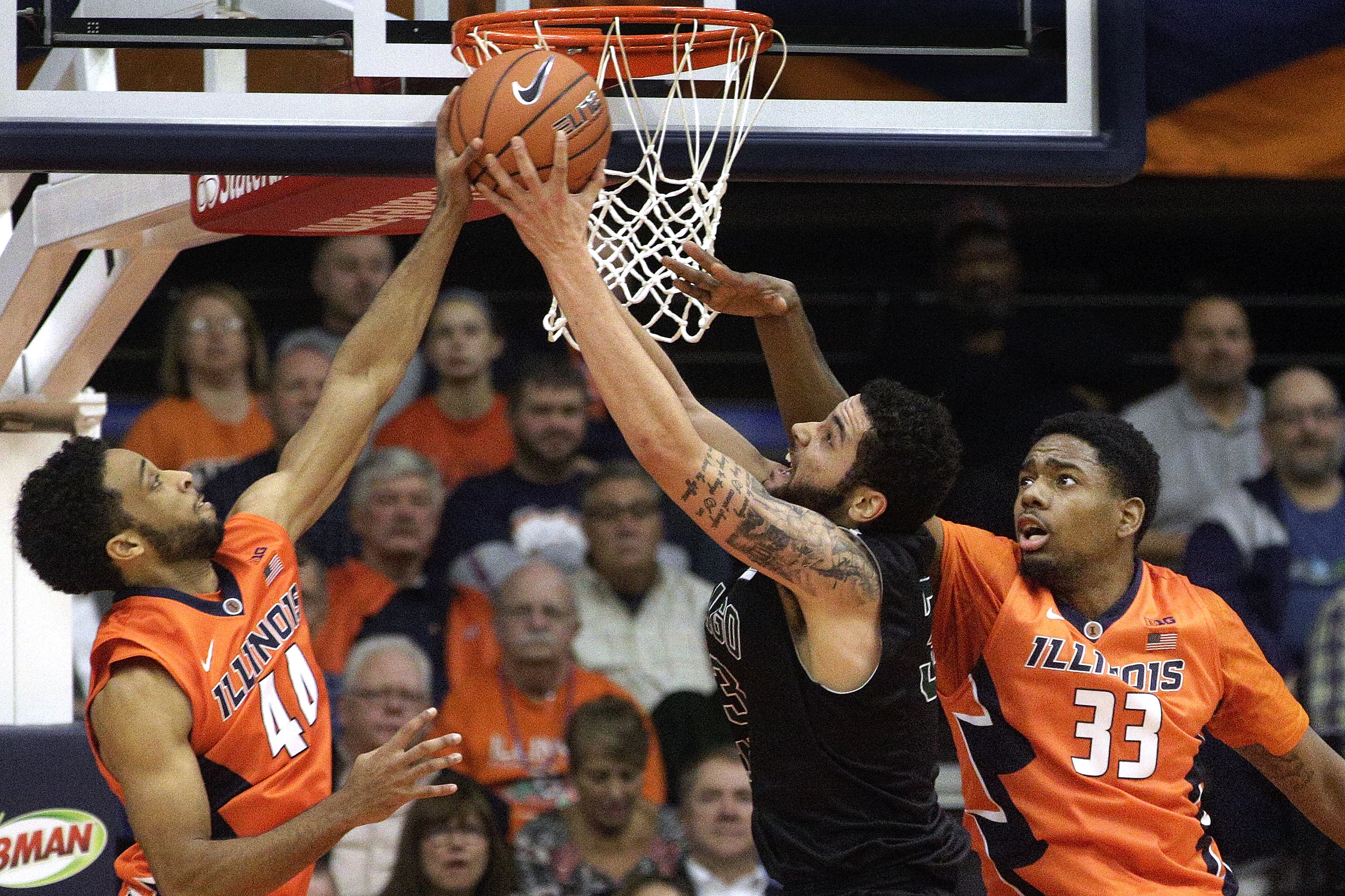 Chicago State forward Jordan Madrid-Andrews, center, goes to the basket against Illinois guard Alex Austin, left, and Illinois forward Mike Thorne Jr. (33) during the first half of an NCAA  college basketball game at the Prairie Capital Convention Center,
