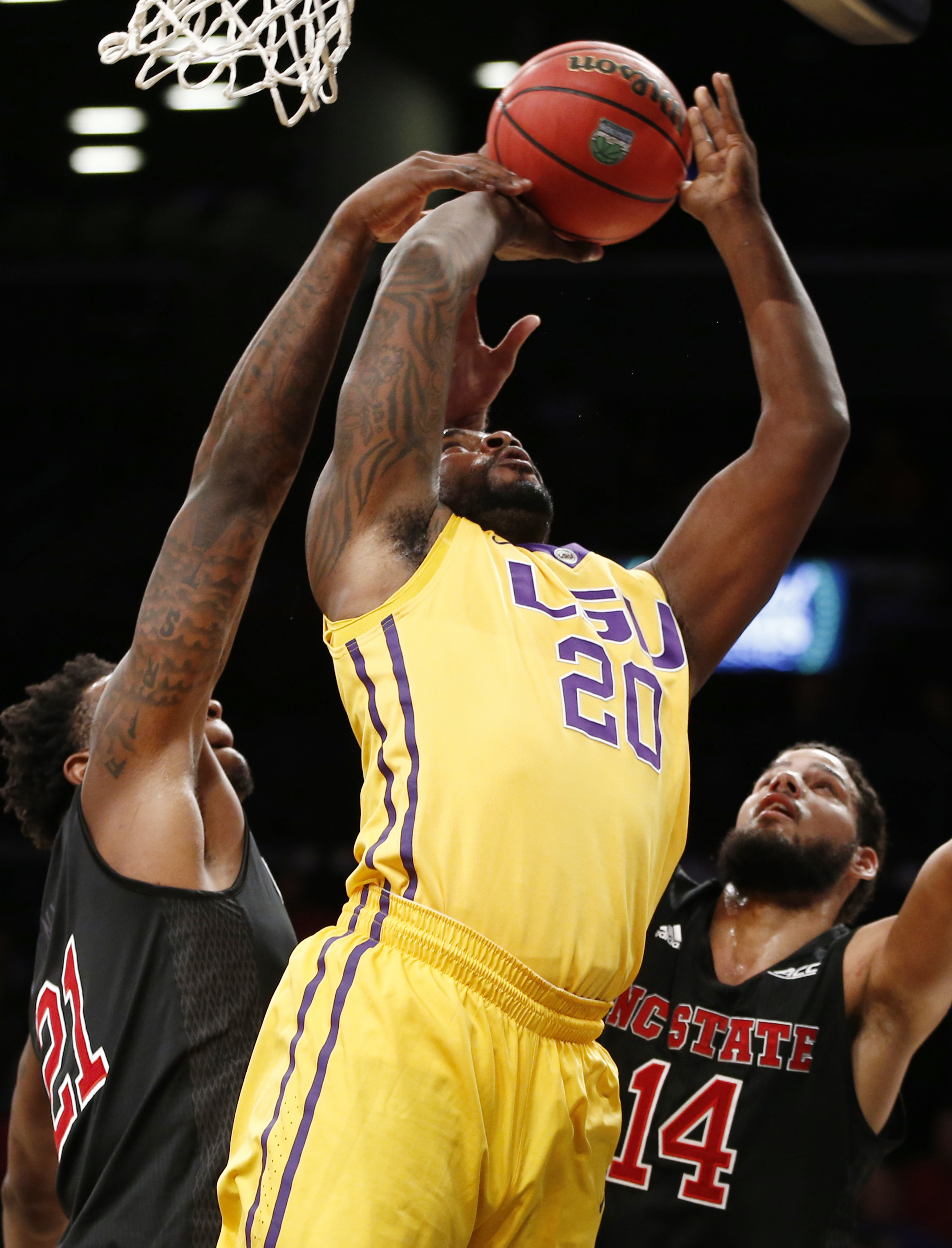 North Carolina State forward BeeJay Anya (21) and guard Caleb Martin (14) defend LSU forward Brian Bridgewater (20), who loses the ball during the first half of an NCAA college basketball game for third place in the Legends Classic, Tuesday, Nov. 24, 2015