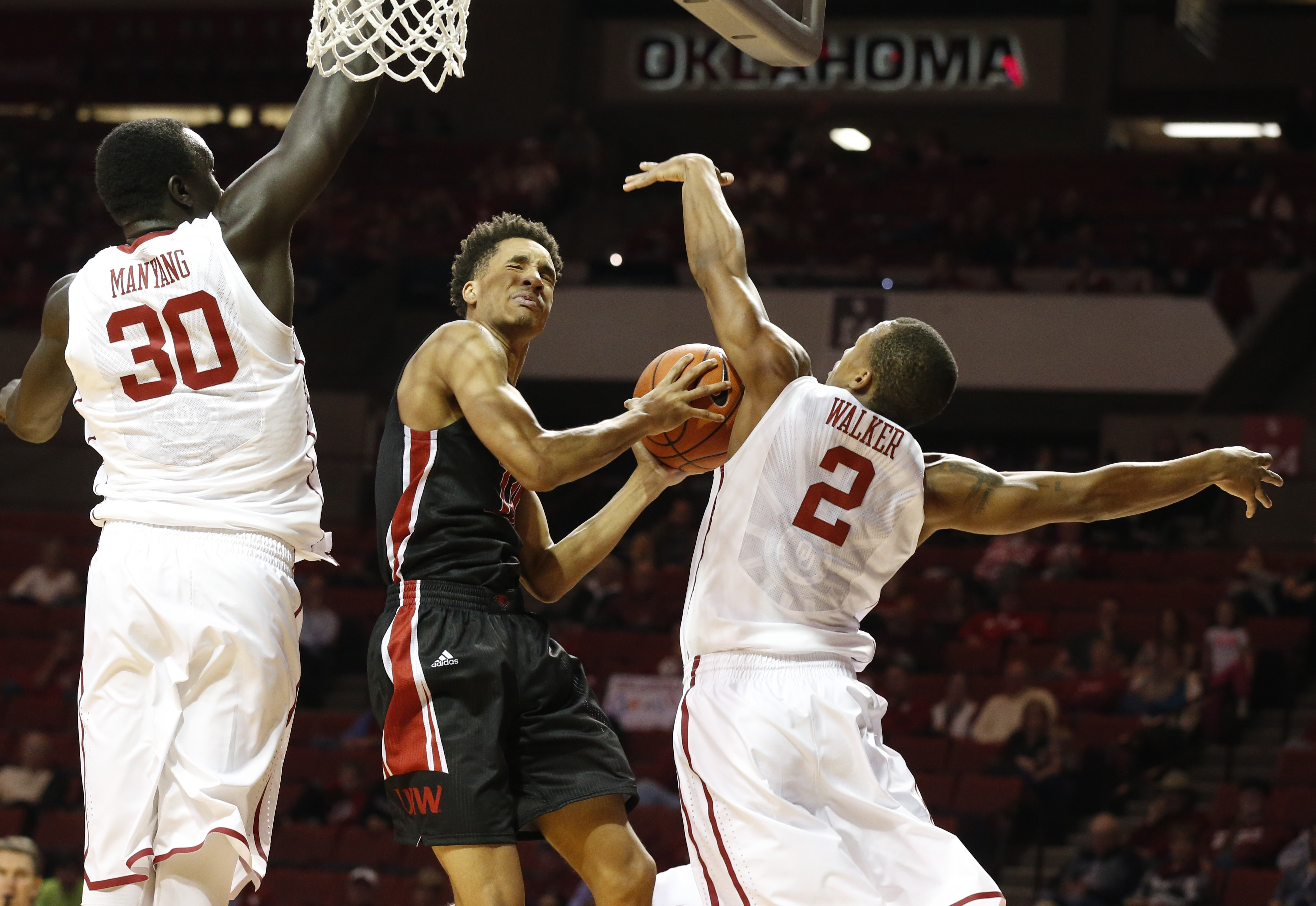 Incarnate Word guard Tyler Singleton, center, shoots between Oklahoma center Akolda Manyang (30) and guard Dinjiyl Walker (2) during the first half of an NCAA college basketball game in Norman, Okla., Tuesday, Nov. 24, 2015. (AP Photo/Sue Ogrocki)