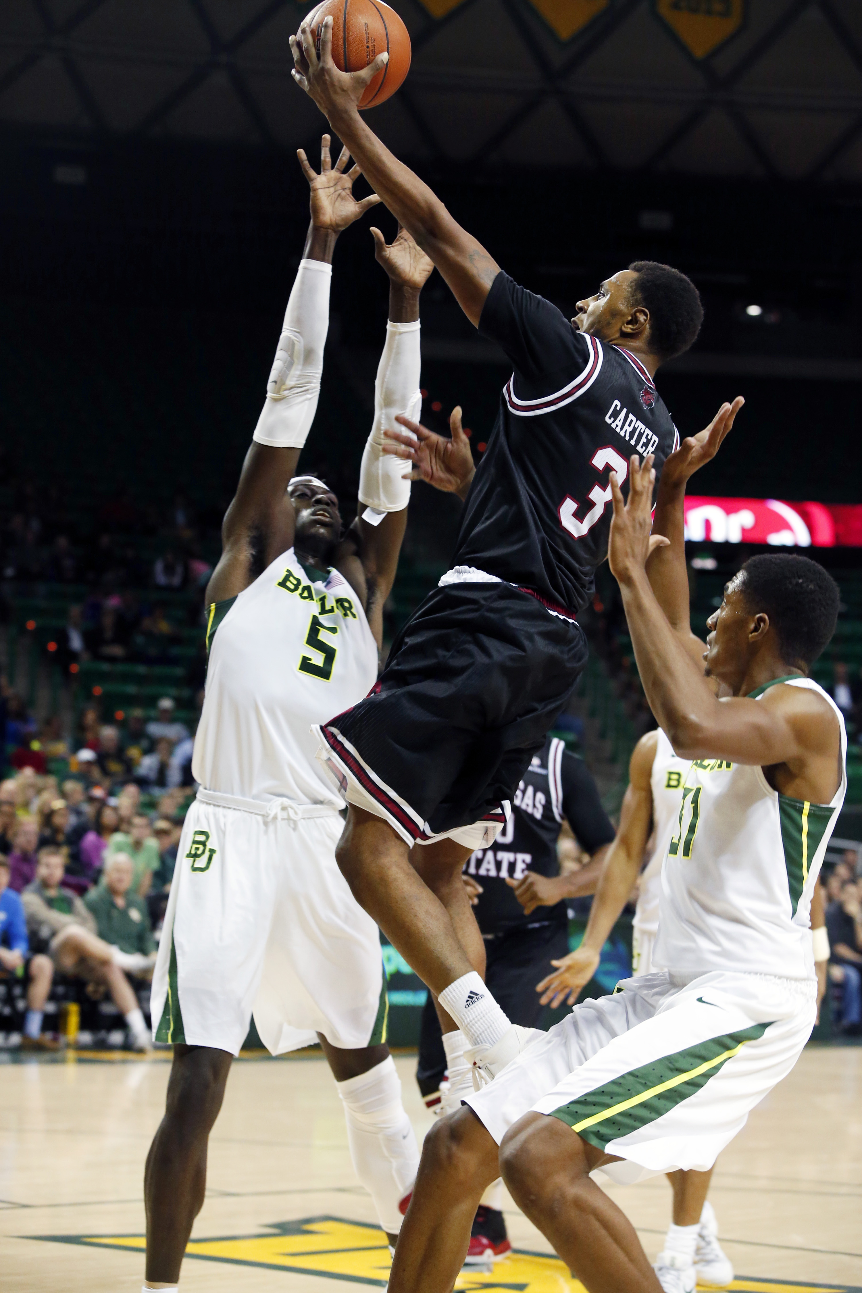 Arkansas State guard Devin Carter (3), center, scores past Baylor forward Johnathan Motley (5), left, and forward Terry Maston (31), right, in the second half of an NCAA college basketball game, Friday, Nov. 27, 2015, in Waco, Texas. (Rod Aydelotte/Waco T