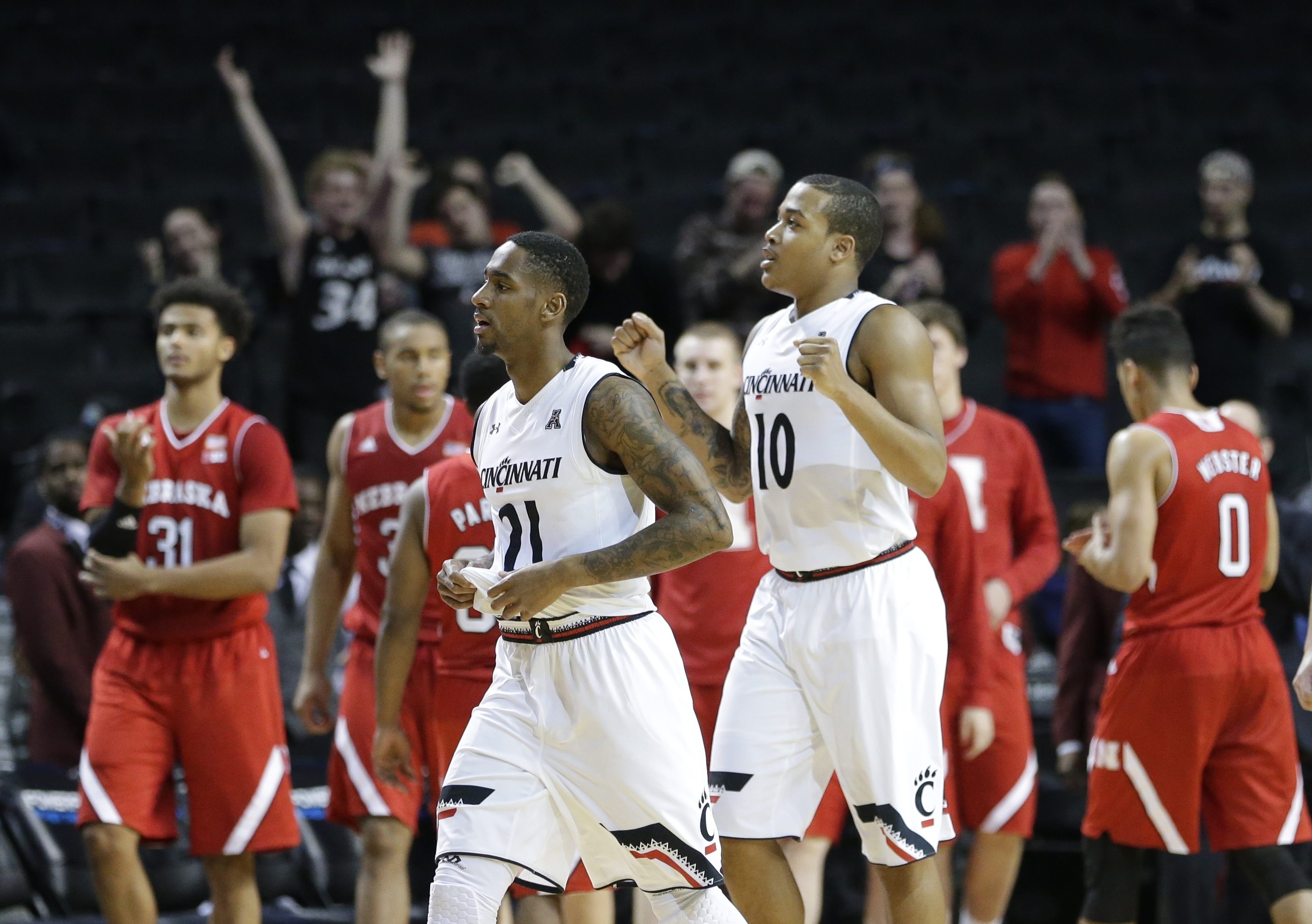 Cincinnati's Farad Cobb (21) and Troy Caupain (10) celebrate after an NCAA college basketball game against Nebraska Friday, Nov. 27, 2015, in New York. Cincinnati won 65-61.(AP Photo/Frank Franklin II)