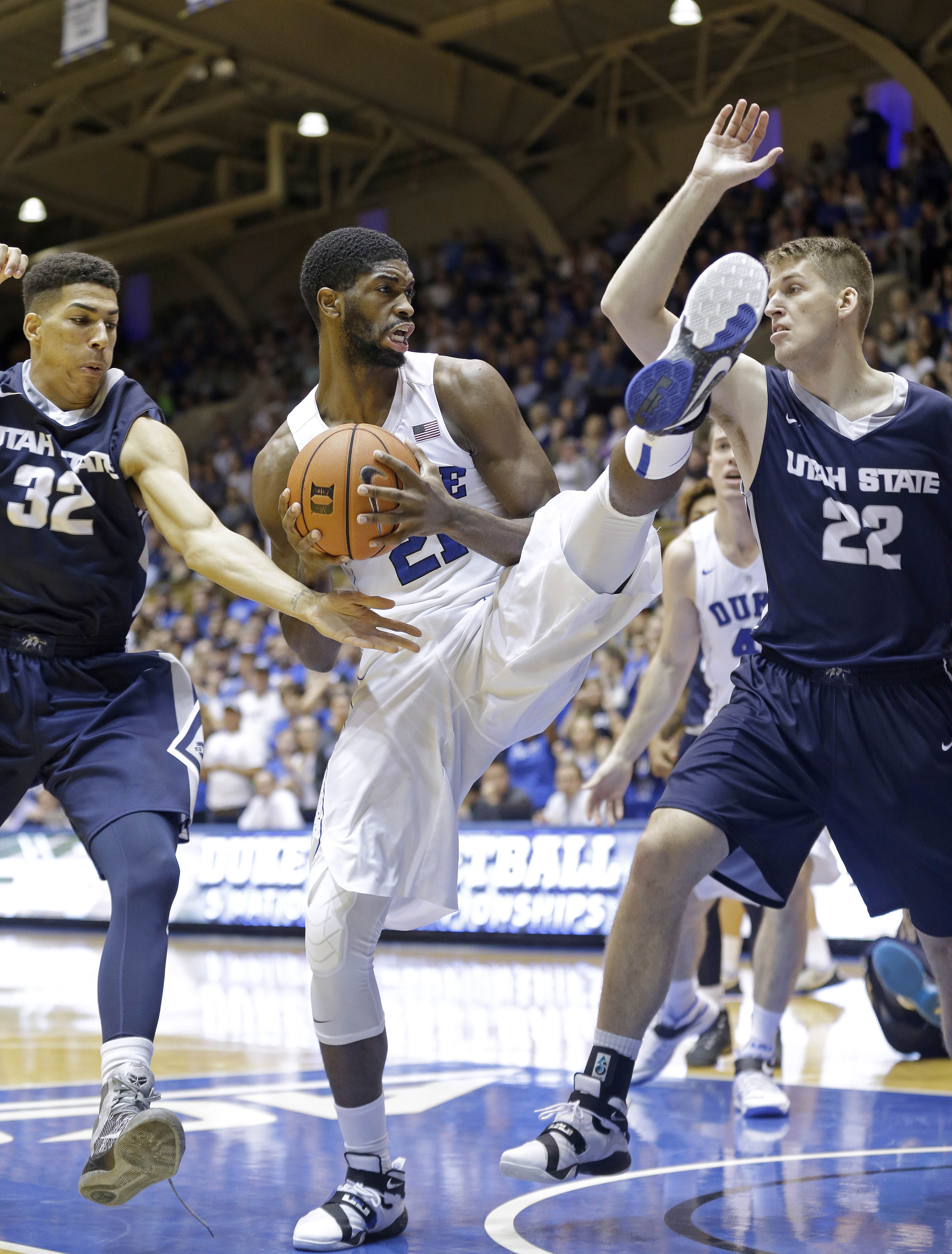 Duke's Amile Jefferson, center, grabs a rebound as Utah State's Grayson Moore (32) and Quinn Taylor (22) defend during the first half of an NCAA college basketball game in Durham, N.C., Sunday, Nov. 29, 2015. (AP Photo/Gerry Broome)
