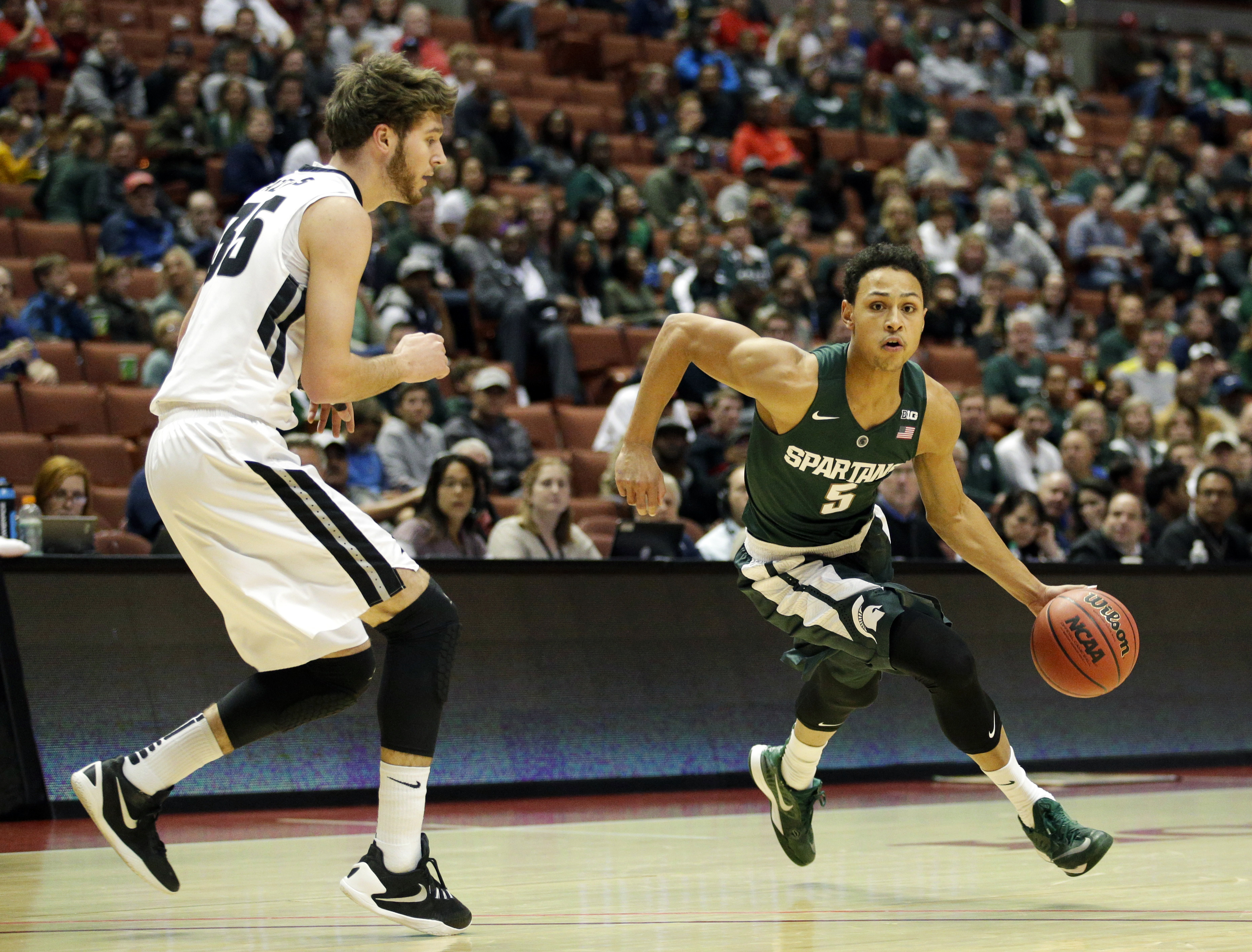 Michigan State guard Bryn Forbes, right, dribbles as Providence guard Ryan Fazekas watches during the first half of an NCAA college basketball game at the Wooden Legacy tournament, Sunday, Nov. 29, 2015, in Anaheim, Calif. (AP Photo/Jae C. Hong)