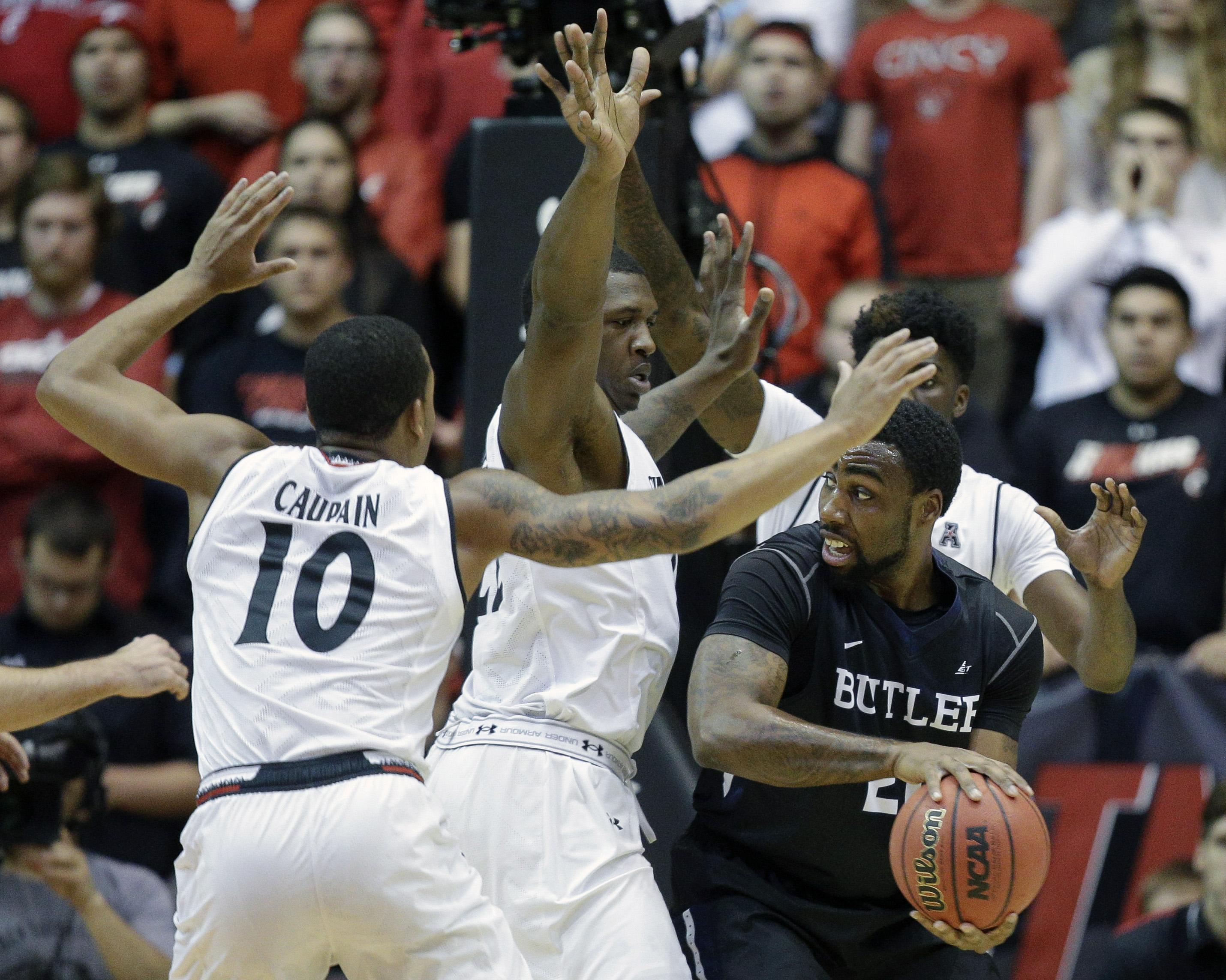 Butler's Roosevelt Jones (21) looks to pass around Cincinnati's Coreontae DeBerry, center, and Troy Caupain (10) in the first half of an NCAA college basketball game, Wednesday, Dec. 2, 2015, in Cincinnati. (AP Photo/John Minchillo)