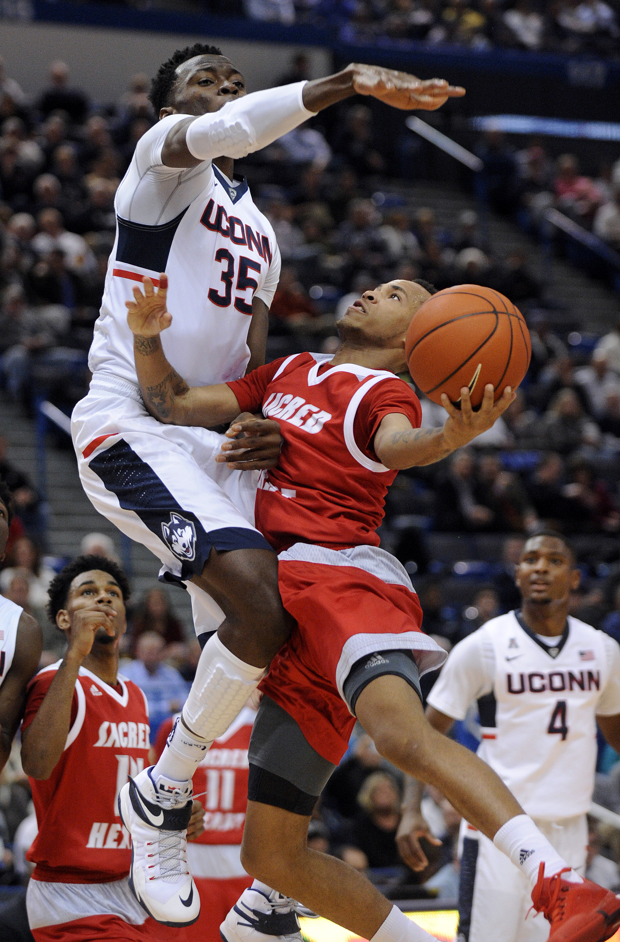 Connecticut's Amida Brimah (35) guards Sacred Heart's Cane Broome during the first half of an NCAA college basketball game in Hartford, Conn., on Wednesday, Dec. 2, 2015. (AP Photo/Fred Beckham)