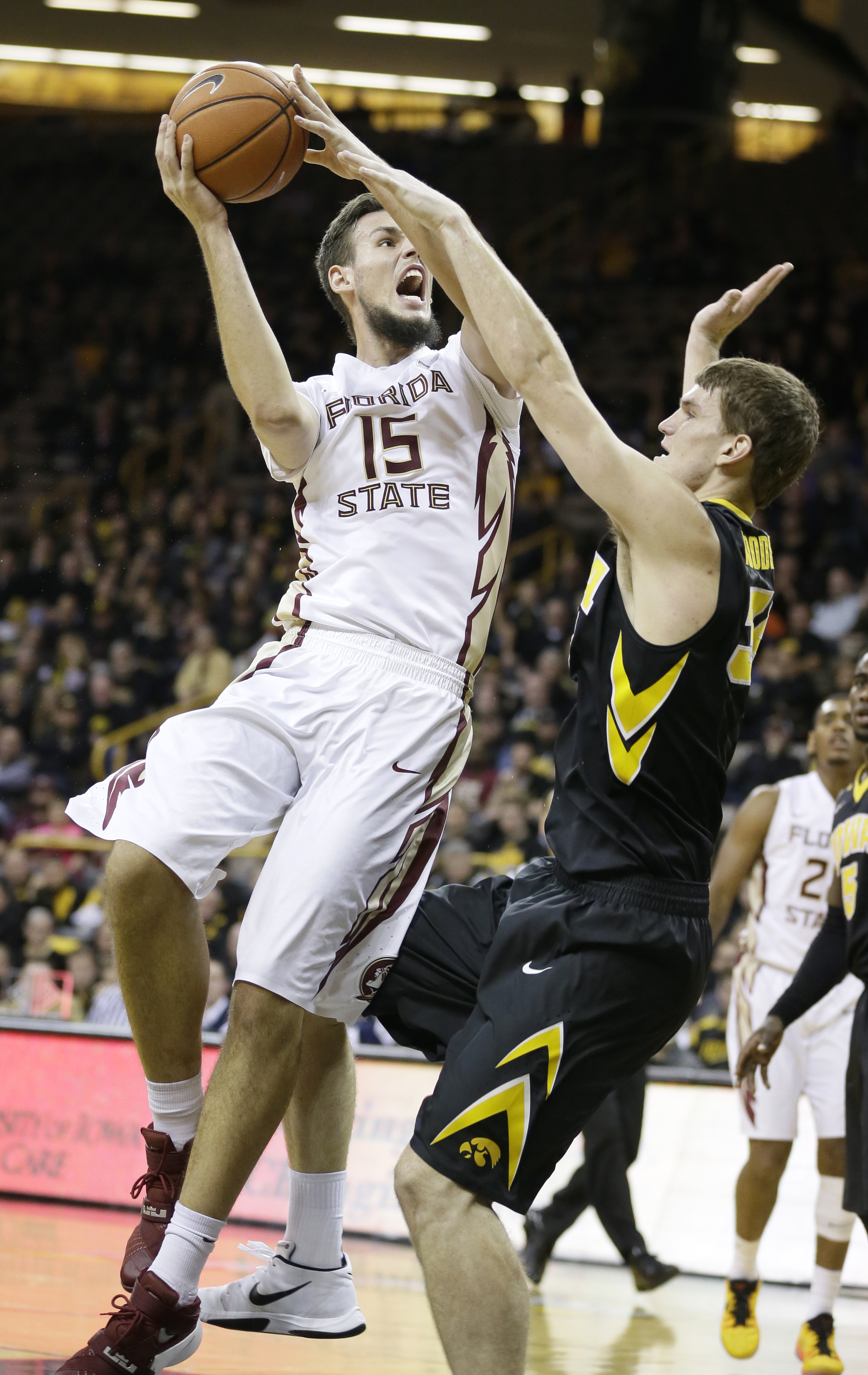 Florida State center Boris Bojanovsky is fouled by Iowa center Adam Woodbury, right, while driving to the basket during the first half of an NCAA college basketball game, Wednesday, Dec. 2, 2015, in Iowa City, Iowa. (AP Photo/Charlie Neibergall)
