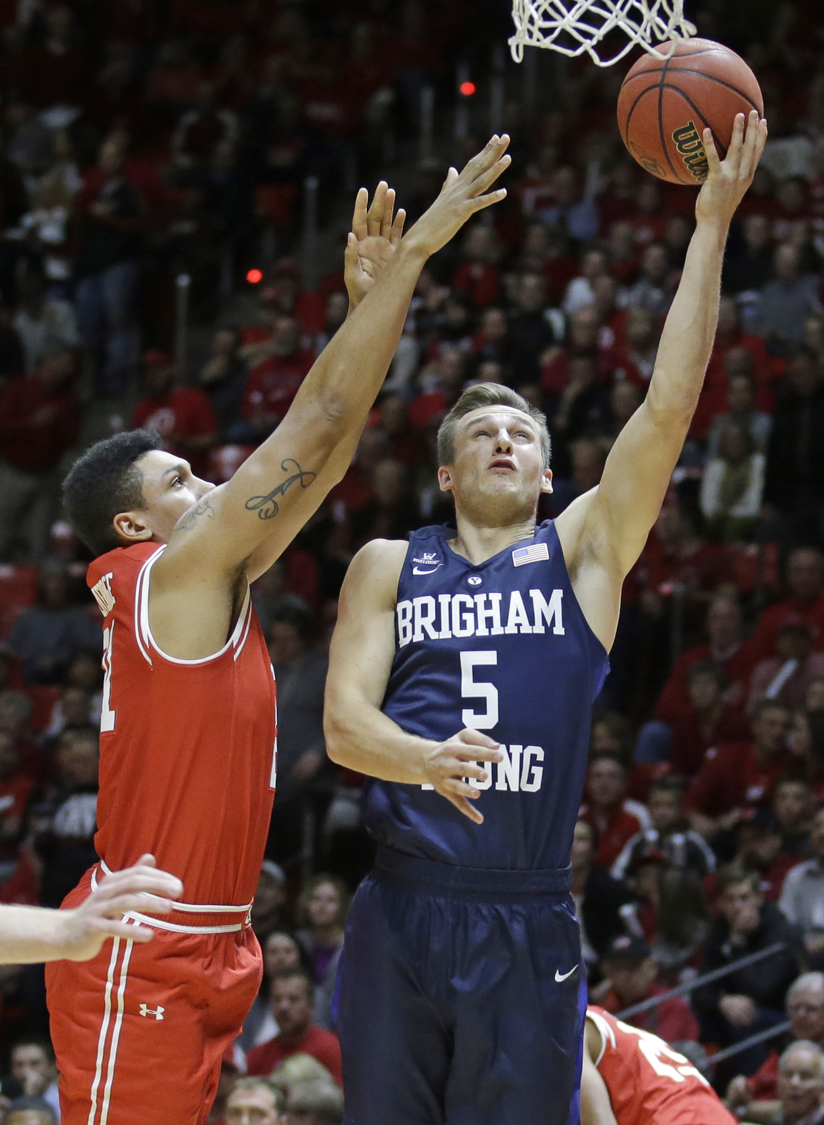 BYU guard Kyle Collinsworth (5) lays the ball up as Utah forward Jordan Loveridge, right, defends in the first half of an NCAA college basketball game Wednesday, Dec. 2, 2015, in Salt Lake City. (AP Photo/Rick Bowmer)