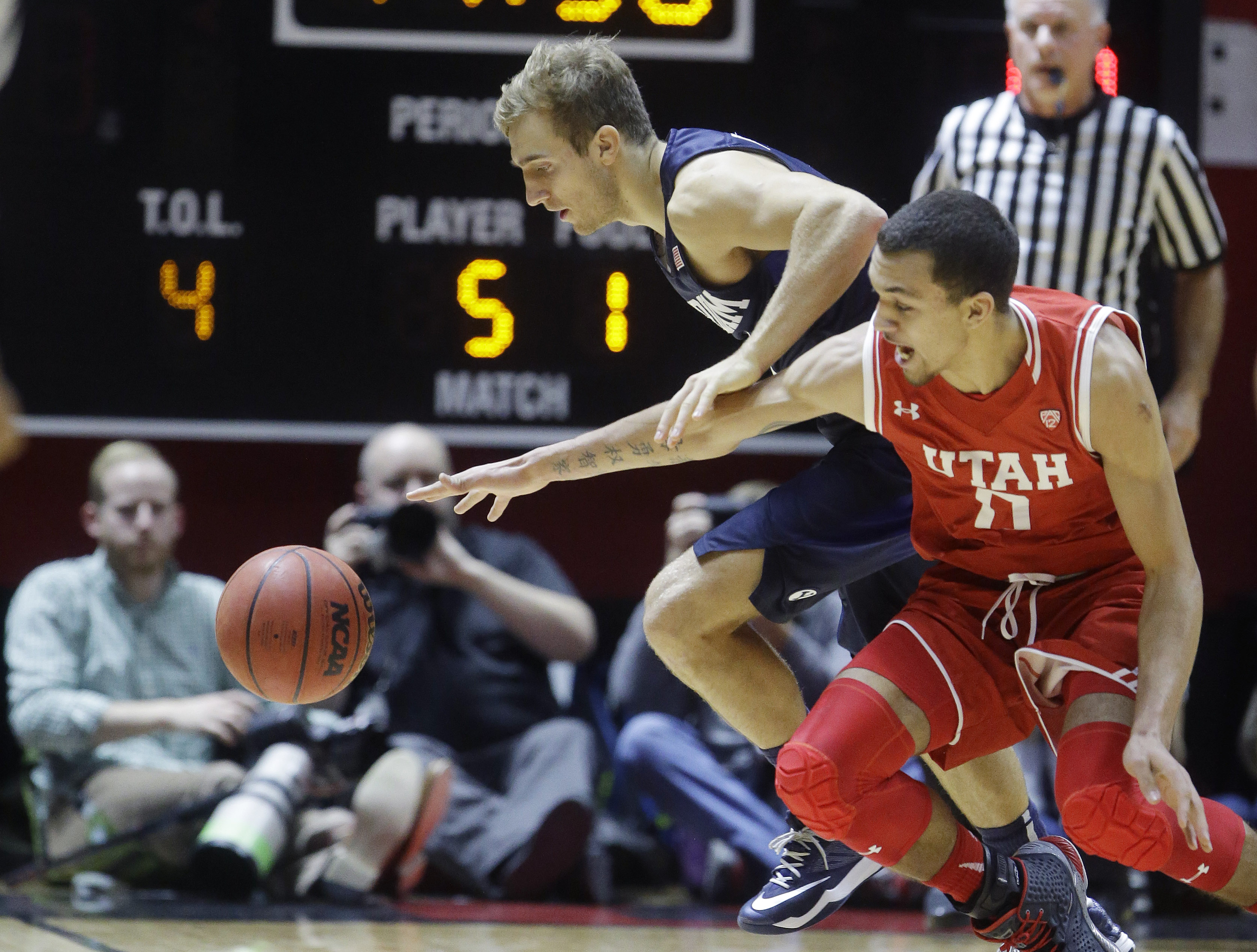 BYU guard Chase Fischer, left, and Utah forward Brekkott Chapman (0) battle for a loose ball in the first half during an NCAA college basketball game, Wednesday, Dec. 2, 2015, in Salt Lake City. (AP Photo/Rick Bowmer)