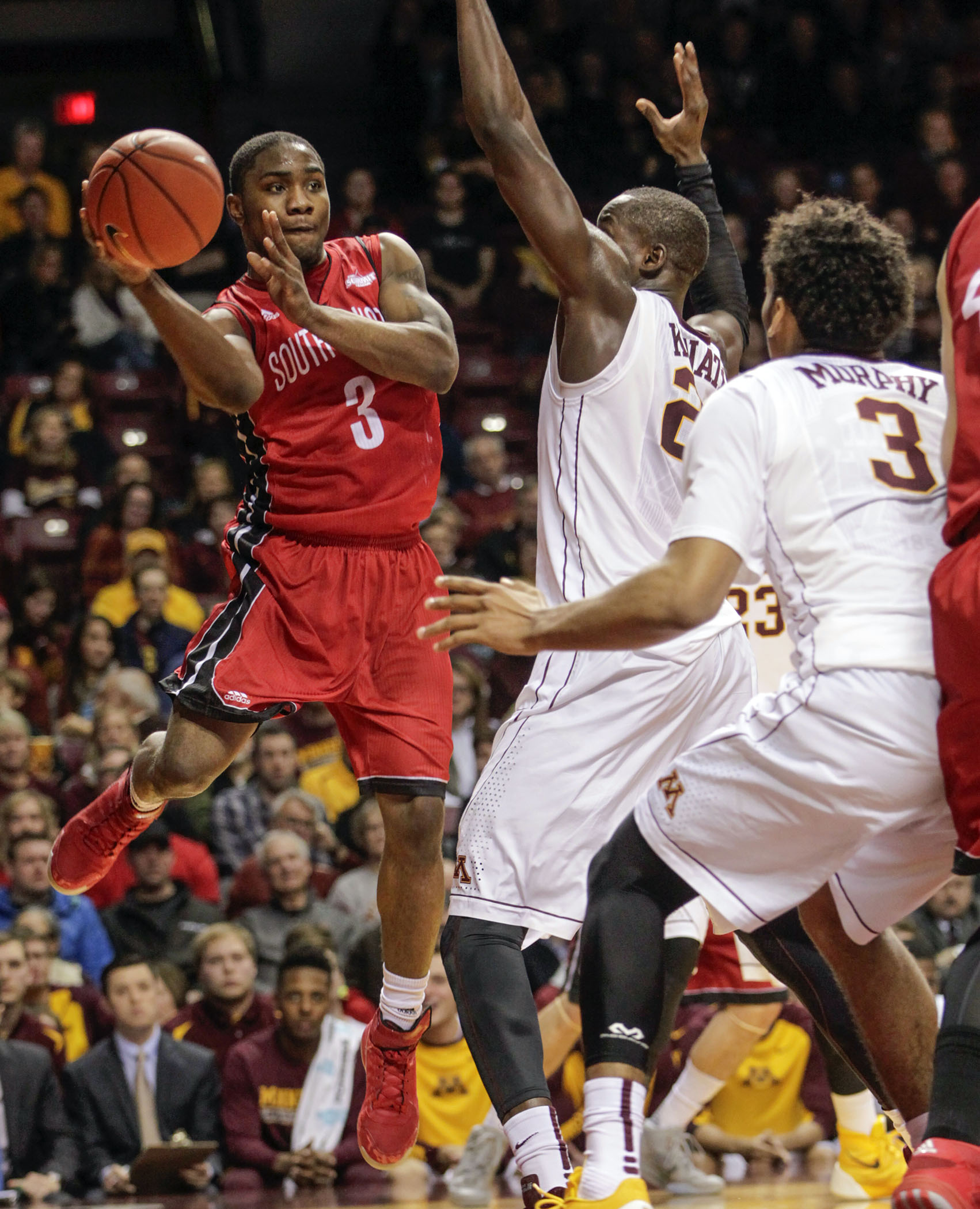 South Dakota guard Shy McClelland (3) looks to pass around Minnesota's Charles Buggs (23) and Jordan Murphy (3) during the first half of an NCAA college basketball game, Saturday, Dec. 5, 2015, in Minneapolis. AP Photo/Paul Battaglia)